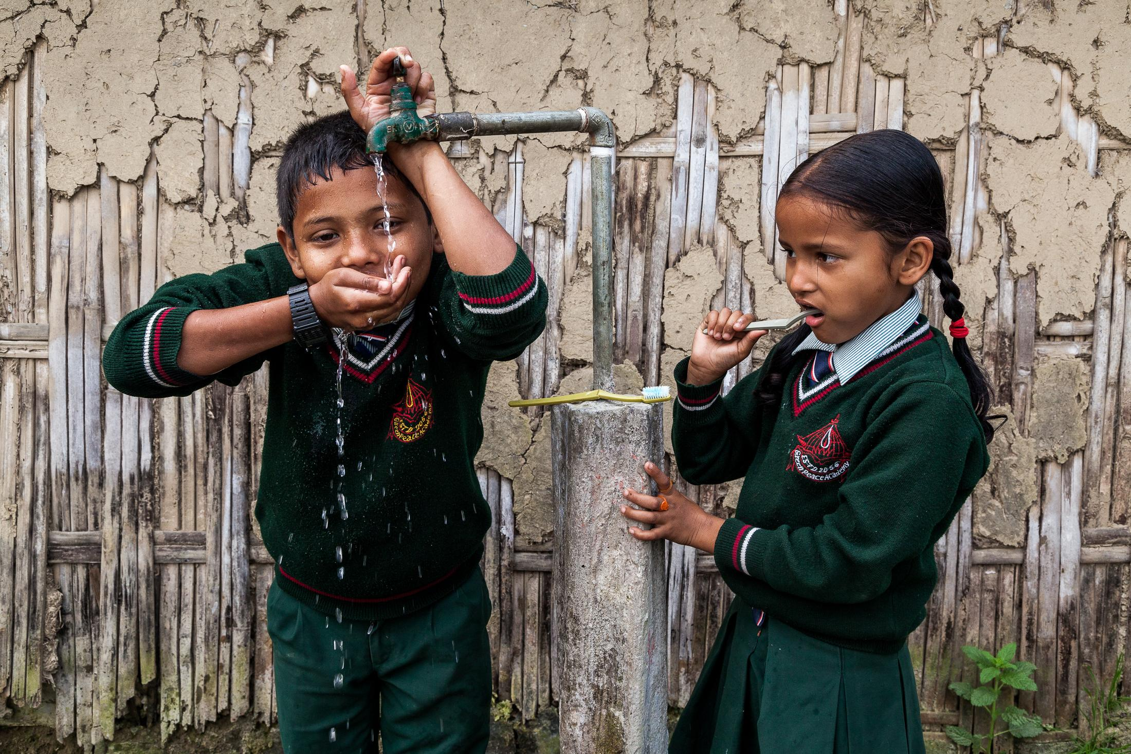 ITAHARI, NEPAL - February 25, 2015: Badal (left), 13 years old, drinks water while Barsa (right), 8 years old, brushes her teeth from a water tap installed by the organization Lumanti before going to school in the Pragatitol neighborhood on the outskirts of Itahari, Nepal on February 25, 2015. Despite Nepal's extensive natural resources, access to clean and affordable water remains a problem throughout the country. For many people in the more remote mountains and hills, water sources are often far away and not necessarily safe, and the simple act of fetching water can drain a community's human resources. Photo: © Omar Havana for Water Aid Nepal