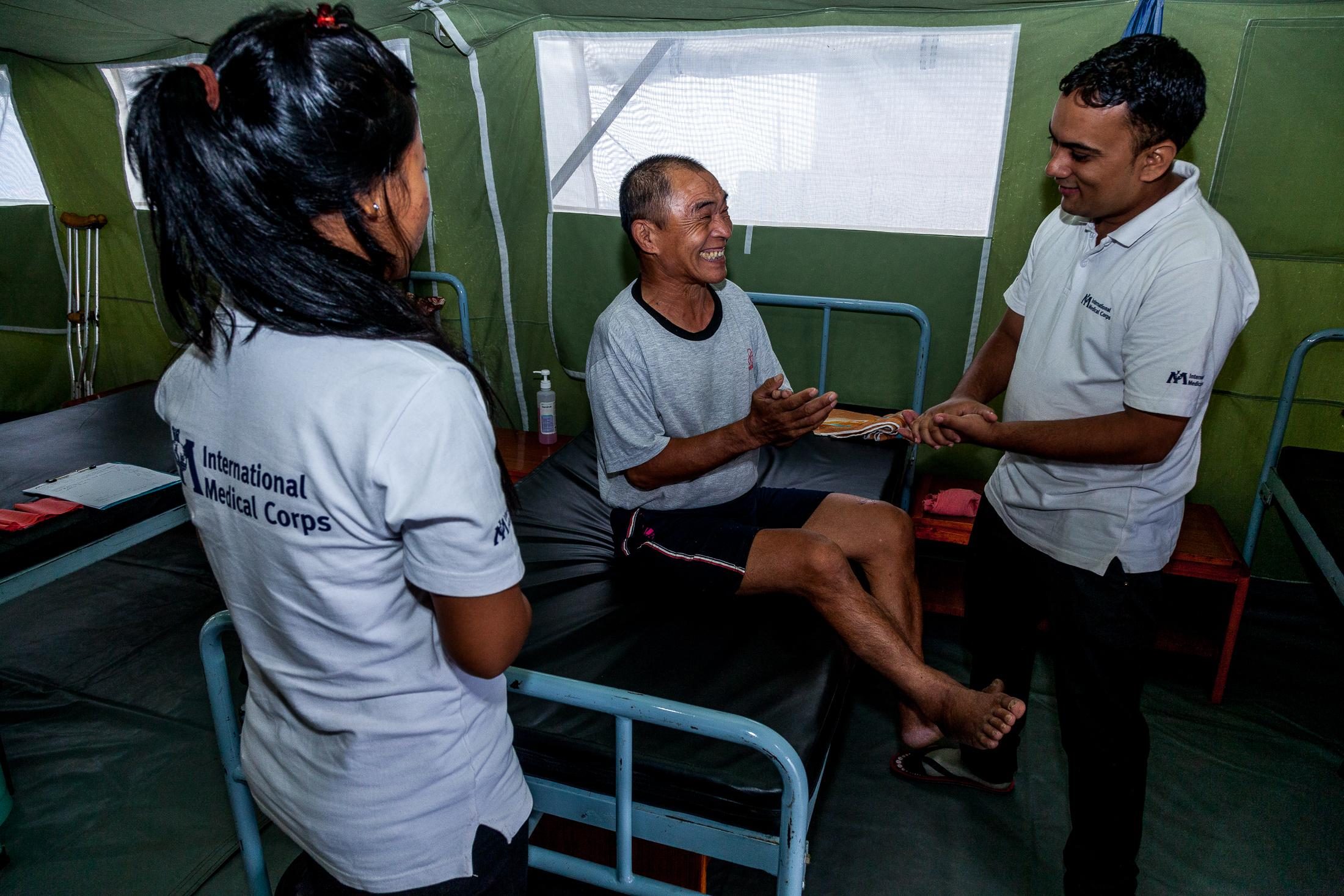 GORKHA, NEPAL - August 21: IMC staff members speak to Dhan Singh Gurung inside the new physiotherapy unit set up by International Medical Corps in Gorkha, Nepal. On 25 April when the earthquake struck Nepal, Dhan Singh Gurung was herding cattle with his friends in Gumda, a village bordering the epicenter of the earthquake. Before he could run, he was swept off his feet by an avalanche – which saved his life. 'The avalanche tossed me into a nook on the side of a cliff,' Gurung explains. 'Squinting through dust, I witnessed the landslide running its course above me. I had been spared.' Photo: © Omar Havana for International Medical Corps