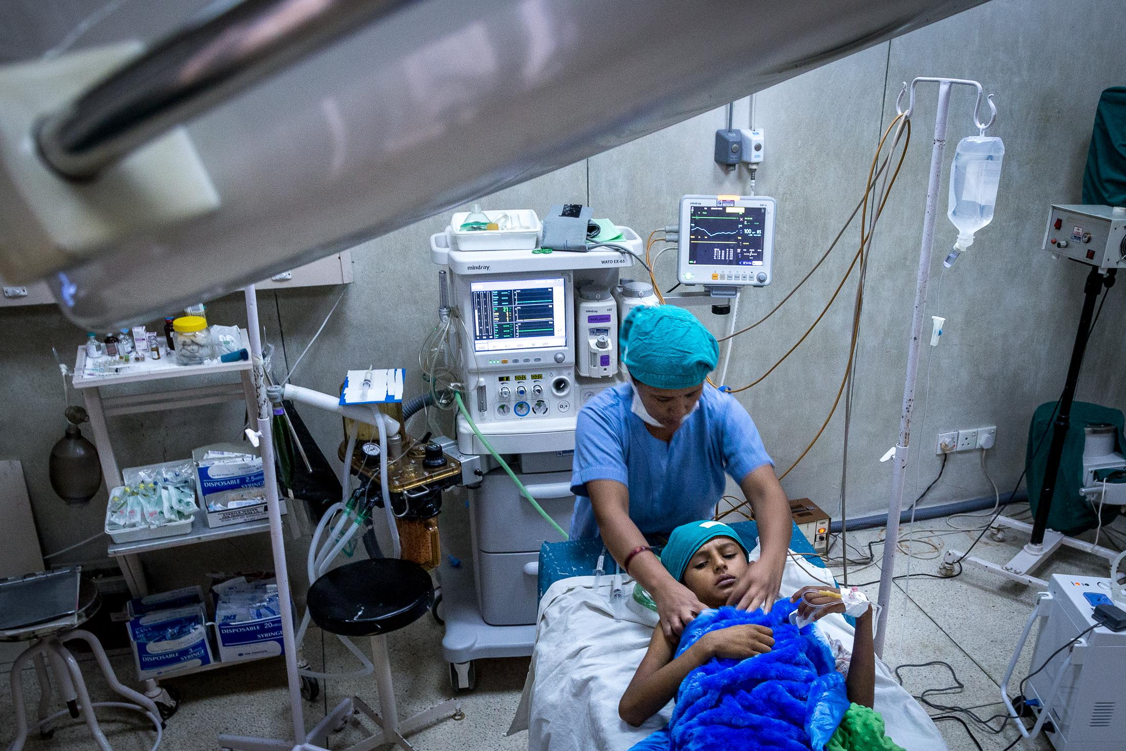 BANEPA, NEPAL - JULY 07, 2015: A nurse prepares a young boy for surgery for his injuries from the earthquake in a local hospital on July 07, 2015 in Banepa, Nepal. According to Handicap International, more than 65% of the people injured during the earthquake suffered fractures and 12% suffered injuries of the spinal cord. Photo: © Omar Havana