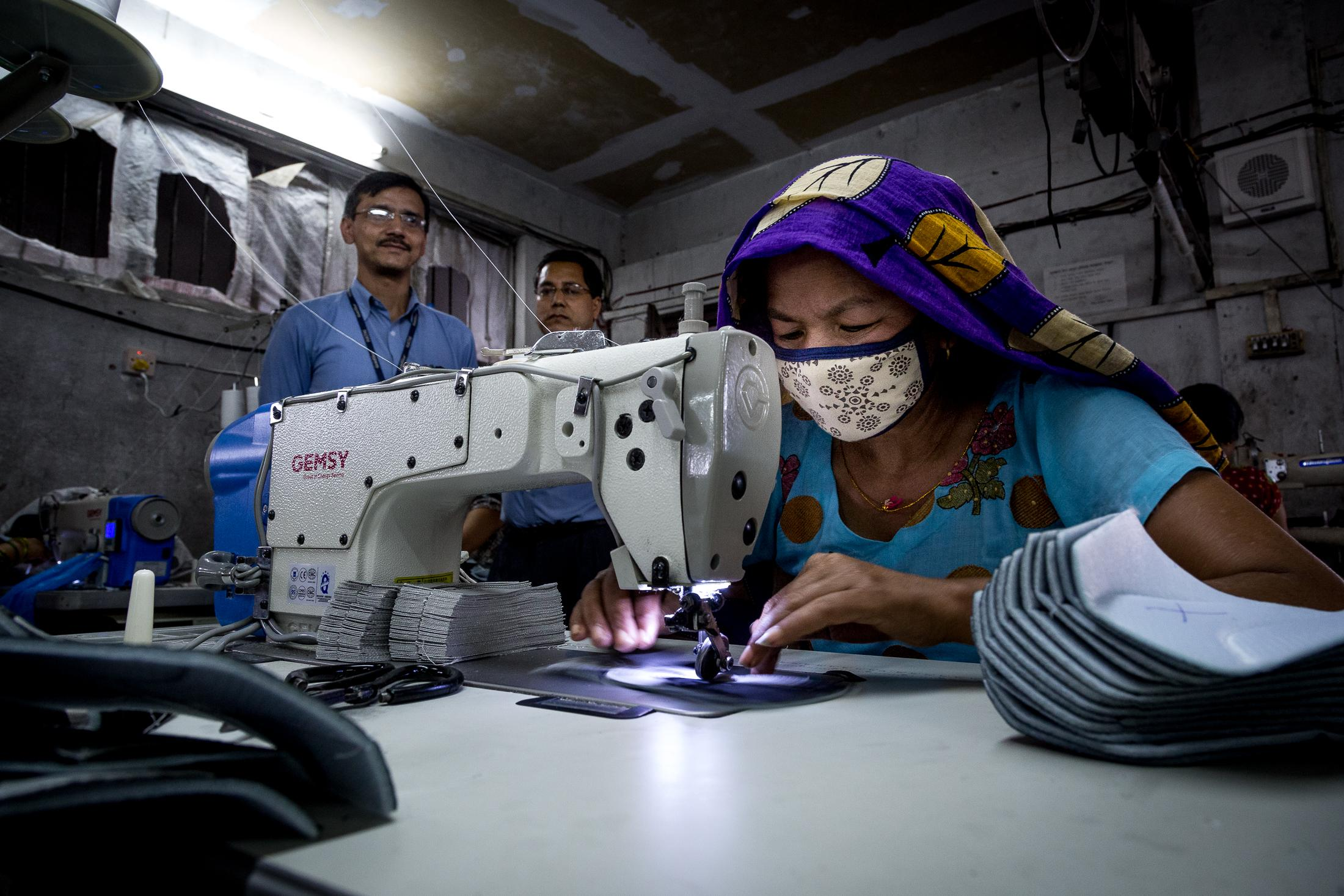 KATHMANDU, NEPAL - JULY 13, 2015: A woman sews shoes under the attention of her supervisors in a factory on July 13, 2015 in Kathmandu, Nepal. Photo: © Omar Havana for ILO