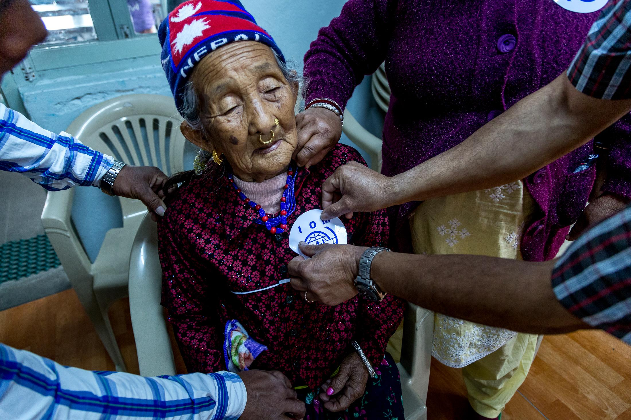 KATHMANDU, NEPAL - MARCH 23, 2015: An IOM staff member places an IOM identification sticker in Dhan Maya Rai's jacket, 87 years old, while she attends her departure briefing minutes before traveling to Kathmandu airport to be resettled in the United States on March 23, 2015 in Kathmandu, Nepal. Photo: © Omar Havana