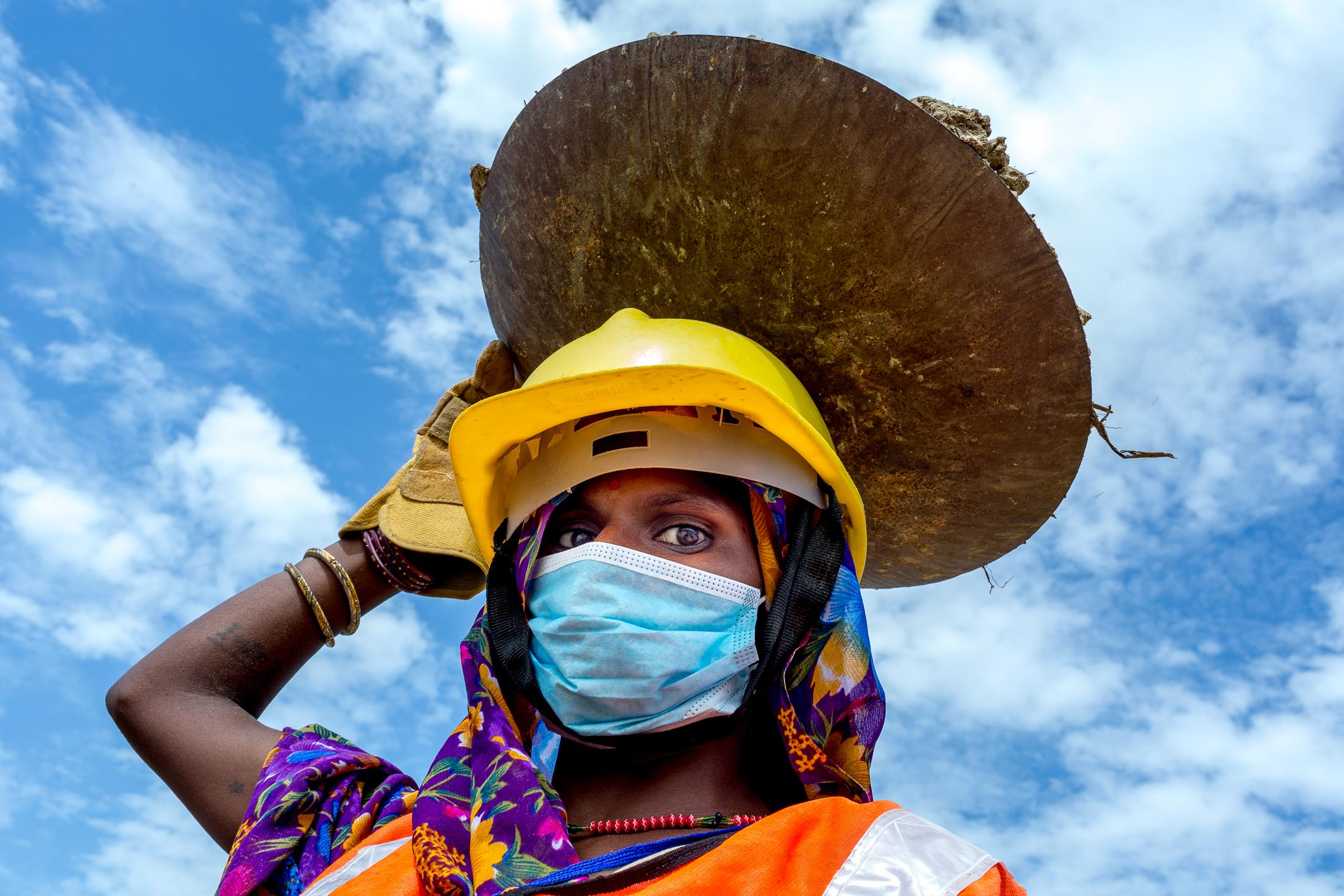 JANAKPUR, NEPAL - JULY 23, 2015: A Maithil woman stands holding a pot filled with sand that she collected while working as road maintenance staff on July 23, 2015 near Janakpur, Nepal. Traditionally, women from the Maithil community have almost never worked in official positions or in the formal economy being economic dependants in their families - first as daughters, then as wives and mothers, and often as widows. Their labor is in service to their husbands' families. But for years, Maithili women have been making strides to gain independence, helped by projects aimed at providing them with income-earning opportunities outside the home. Photo: © Omar Havana for ILO