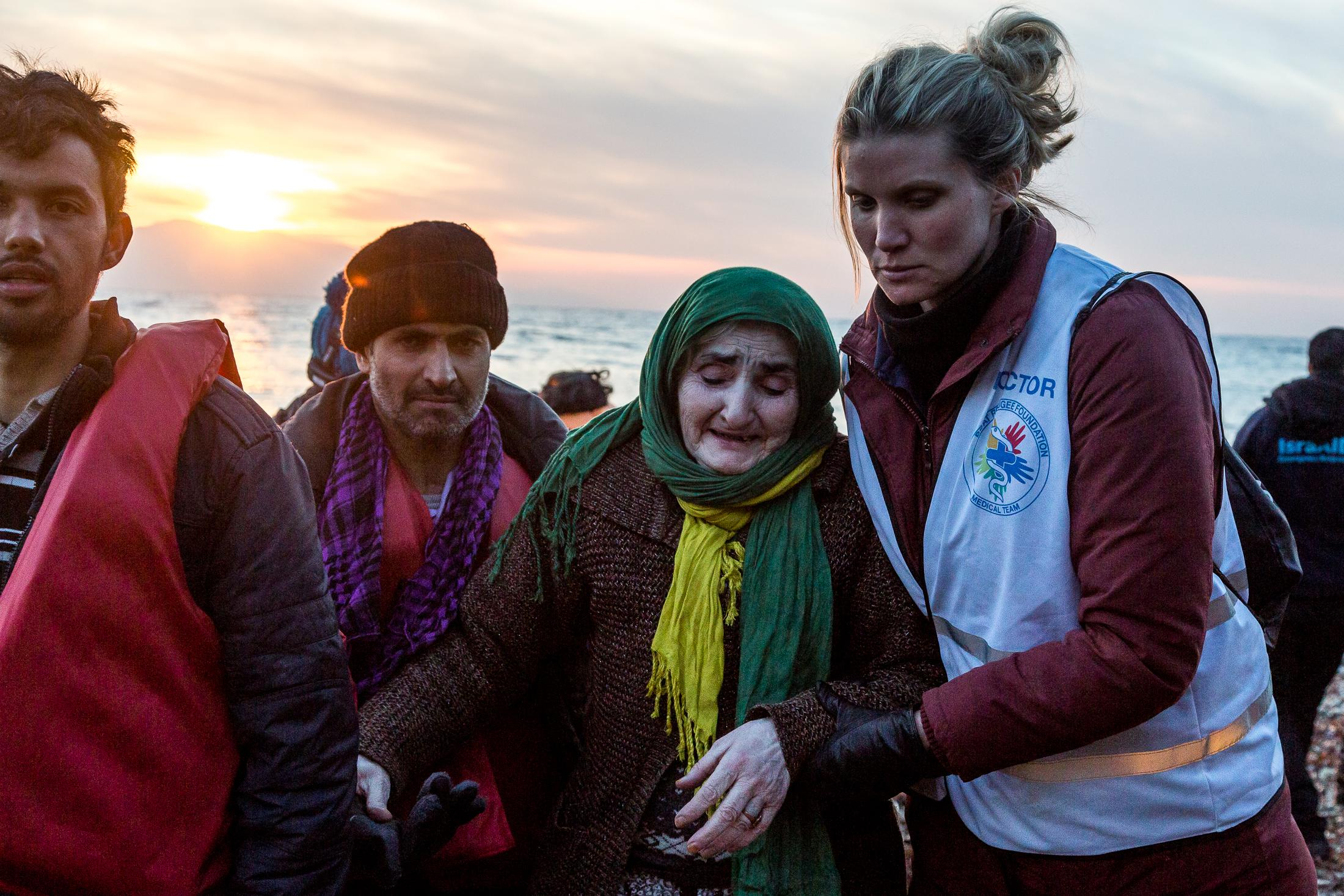 LESVOS, GREECE - FEBRUARY 09, 2016: A doctor helps Sara after getting off a dinghy on which they crossed the Aegean sea from the Turkish coast with dozens of refugees on February 09, 2015 in Lesvos, Greece. A UNHCR survey released last month found that 94% of Syrians and 71% of the Afghans arriving in Greece in January had undertaken the dangerous journey in order to escape conflict and violence in their countries. Photo: © Omar Havana for Action Aid Greece