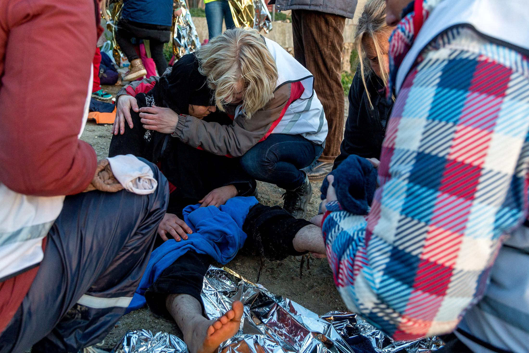 LESVOS, GREECE - FEBRUARY 09, 2016: Volunteers comfort a Syrian refugee suffering from hypothermia after their arrival on a beach in South Lesvos with other refugees and migrants from the Turkish coast on February 09, 2015 in Lesvos, Greece. Photo: © Omar Havana for Action Aid Greece
