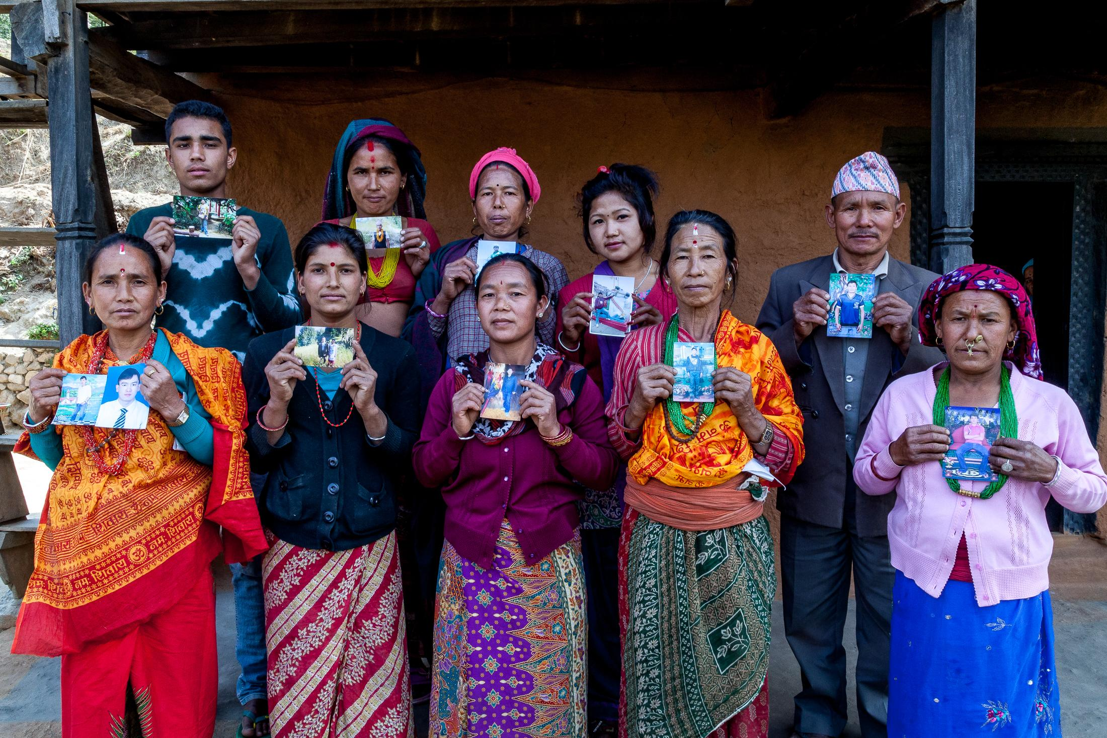 BATASE, NEPAL - FEBRUARY 28, 2015: A group of residents stands holding photos of relatives that have been forced to migrate to other countries for work due to the lack of employment opportunities in Batase, Nepal on February 28, 2015. Photo: © Omar Havana
