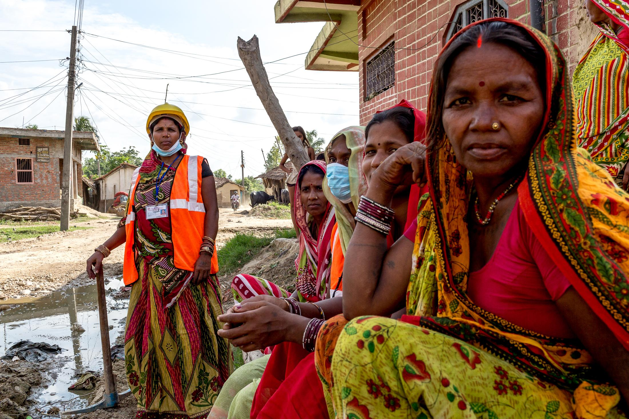 JANAKPUR, NEPAL - JULY 23, 2015: A group of Maithil women sits while chatting to other Maithil women during their break working as road maintenance staff in a rural area on July 23, 2015 near Janakpur, Nepal. Traditionally, women from the Maithil community have almost never worked in official positions or in the formal economy being economic dependants in their families - first as daughters, then as wives and mothers, and often as widows. Their labor is in service to their husbands' families. But for years, Maithili women have been making strides to gain independence, helped by projects aimed at providing them with income-earning opportunities outside the home. Photo: © Omar Havana for ILO
