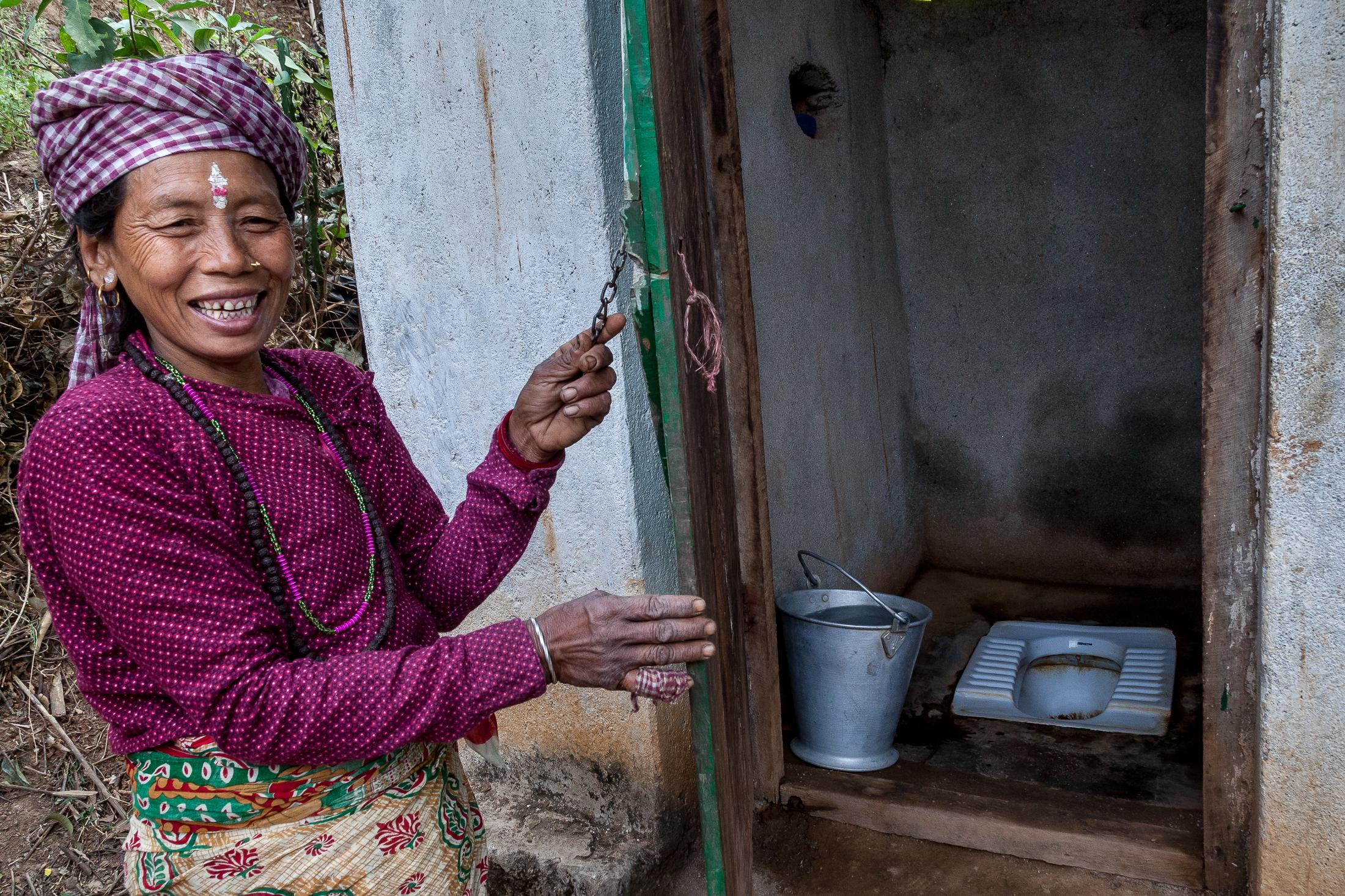 RAUTA KHANITAR, NEPAL - MARCH 01, 2015: Dilmaya Magar, 42 years old, smiles while opening one of the toilets installed by the NEWAH organization in Rauta Khanitar, Nepal on March 01, 2015. Despite Nepal's extensive natural resources, access to clean and affordable water remains a problem throughout the country. For many people in the more remote mountains and hills, water sources are often far away and not necessarily safe, and the simple act of fetching water can drain a community's human resources. Photo: © Omar Havana for Water Aid Nepal