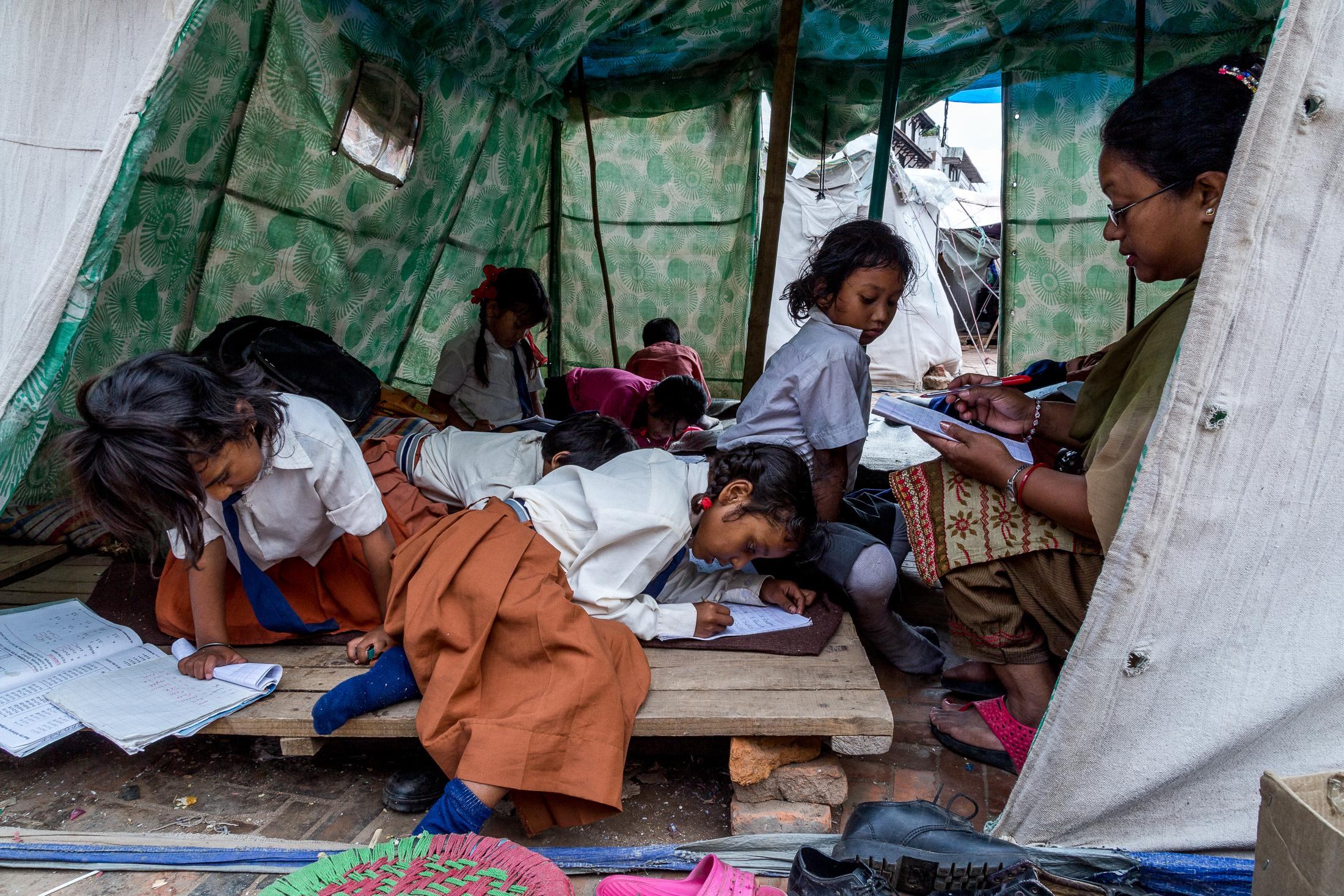 KATHMANDU, NEPAL - JUNE 21, 2015: Young children attend a class inside a tent set up in one of the temporary camps for people who lost their homes in the earthquake that hit Nepal in Kathmandu, Nepal on June 21, 2015. Photo: © Omar Havana
