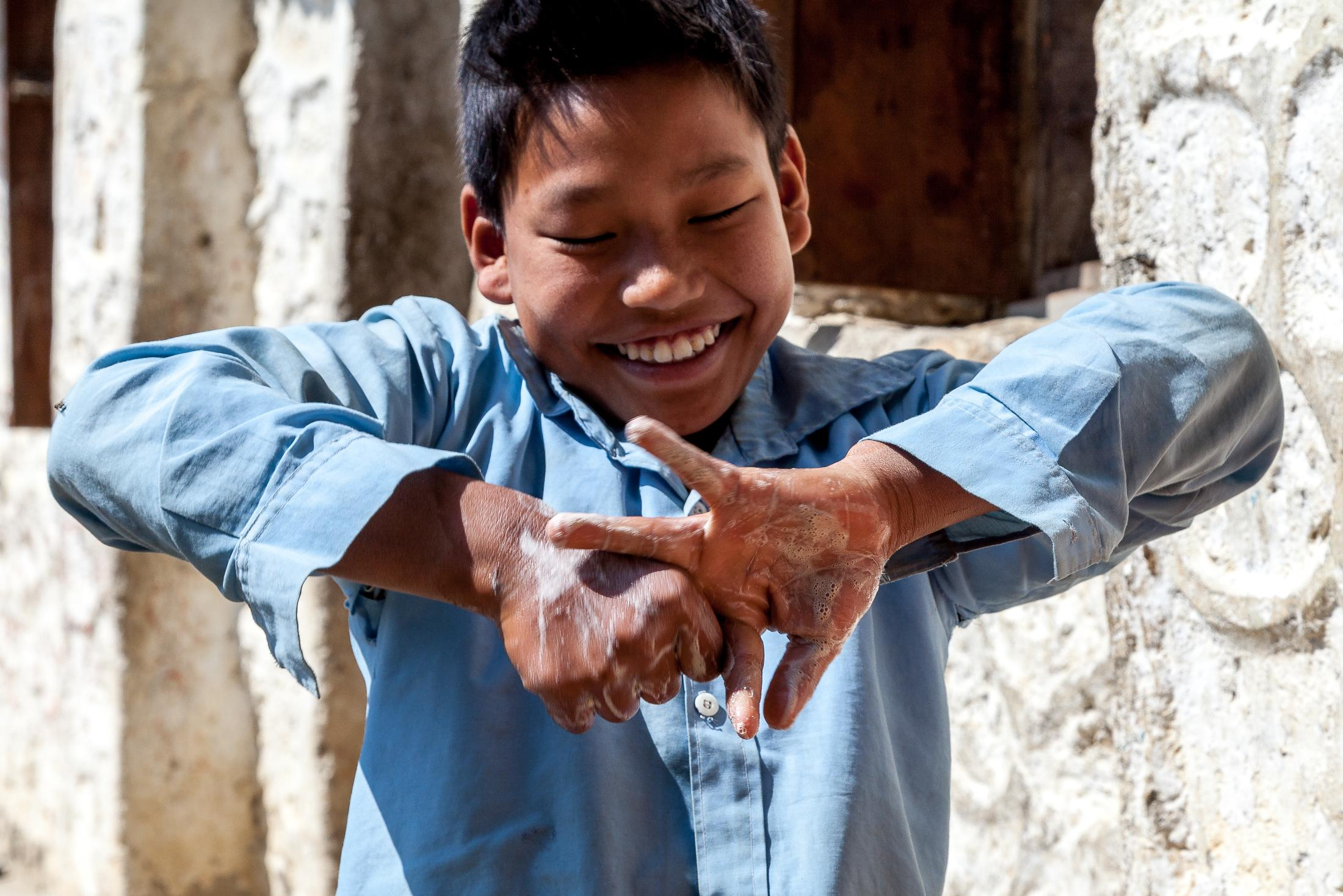 BATASE, NEPAL - FEBRUARY 27, 2015: A young student cleans his hands during an exercise in the local school organized by the NEWAH organization in Batase, Nepal on February 27, 2015. Nepal Water for Health (NEWAH) was established as a local NGO by WaterAid Nepal in 1992. Now running as an independent organization, NEWAH has reached over a million and a half people across 51 of Nepal's 75 districts, supporting communities to put in place comprehensive water and sanitation facilities. Photo: © Omar Havana for WaterAid Nepal