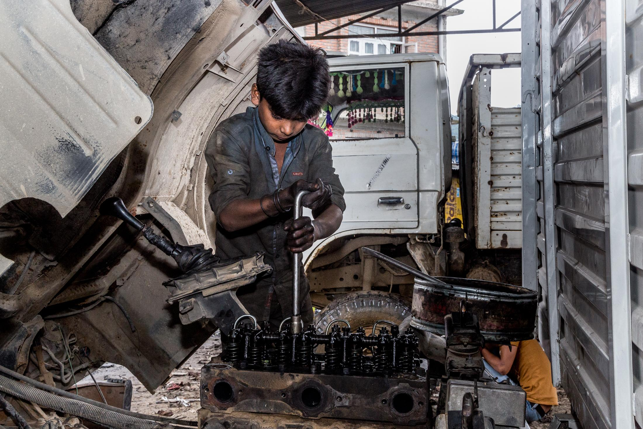 PANAUTI, NEPAL - AUGUST 07, 2015: 12 years-old Mohammad Intaf Alan repairs a truck in the garage that he works on August 07, 2015 in Panauti, Nepal. Photo: © Omar Havana for ILO