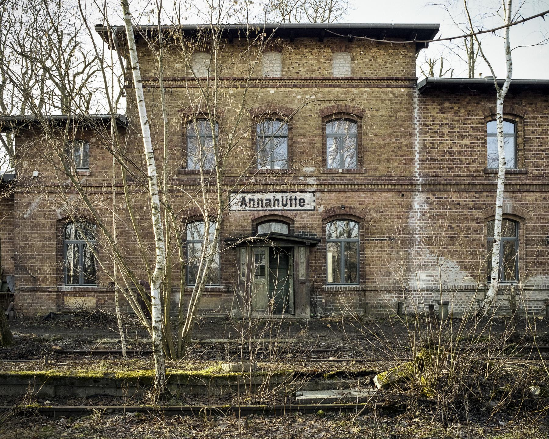 Facade of the main building next to the abandoned platform and rail lines.