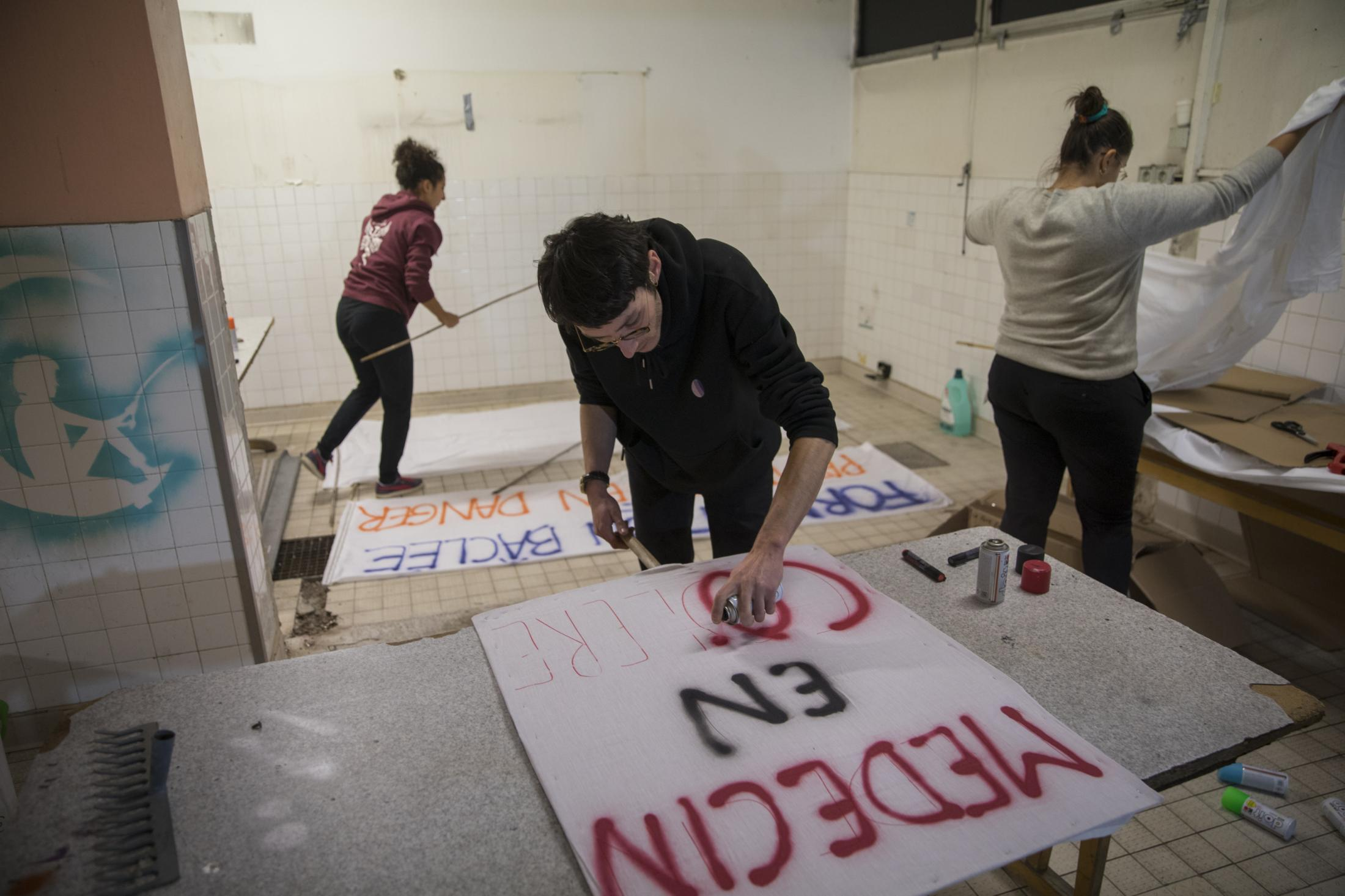 "Vincent Achour, a psychiatry intern and member of the Autonomous Union for Interns of the Hospitals of Marseille paints a sign that reads ""doctors in anger"" before a intern march to raise awareness about their strike. Dec. 9, 2019."