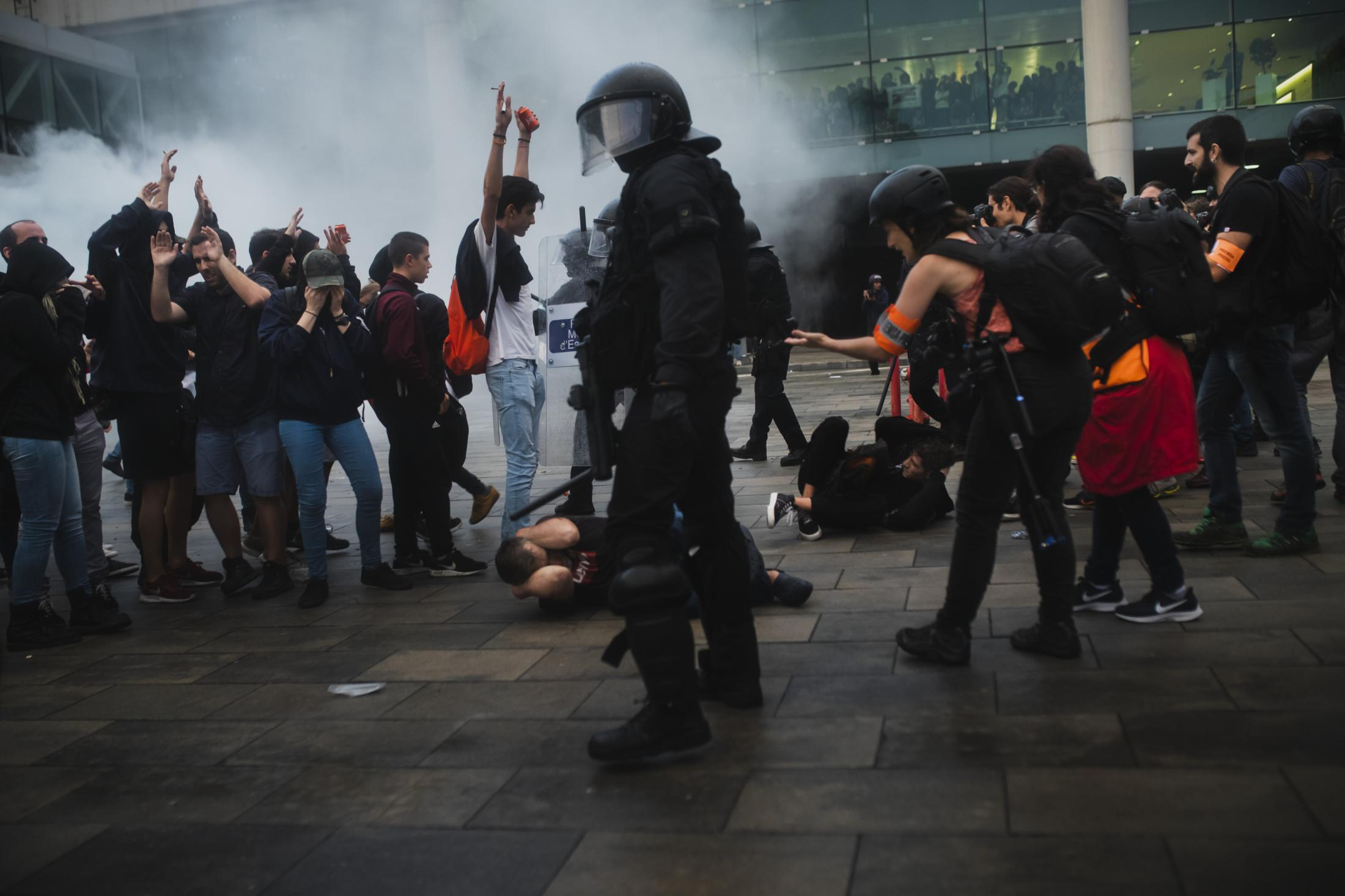"""October 14, 2019. Barcelona, Spain. Riot squads act against protesters at the airport in Barcelona. Spanish authorities decided to begin investigating who is hiding behind the platform and the actions played by a new generation of activists who feel gagged and choose to define themselves """"14-o generation"""". During the protests Police charged, shotted foam bullets, tear gas, rubber bullets, water cannon, and injured journalists. The Commissioner for Human Rights of the Council of Europe has expressed her concern at the reports of attacks on journalists covering the demonstrations in Catalonia, calling on the Spanish government to investigate abuse of power by law enforcement officials. The task of identifying the perpetrator of violence is one of the obligations of the police, even in the case that they are also exercised by the police."""