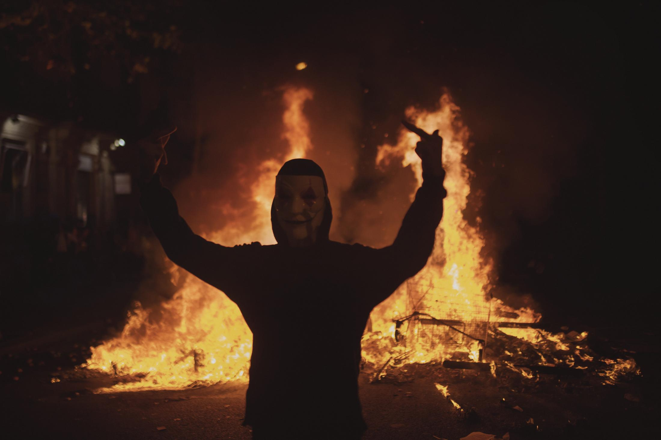 """October 17, 2019. Barcelona, Spain. A masked youth shows his middle finger as a barricade burns behind him. Others masked youths start to hurling cobblestones and flammable bottles, building barricades and setting dozens of bonfires with large garbage bins. The neighbors have taken fire extinguishers from the corridors of their building to try to put out the flames. The streets of Catalonia started to be a place of battle for independence. Businessmen warn about the risk of """"destruction"""" of the Catalan economy. The economic sector shows its concern about the impact on business activity and asks for dialogue to resolve the conflict. In their Twitter account, the police (Mossos) have explained that people are barricading in different streets of Barcelona and asked the citizens not to approach the red areas. They have also reported that protesters have made at least five pyrotechnic launches against the helicopter that flies over Barcelona to help control the protest"""