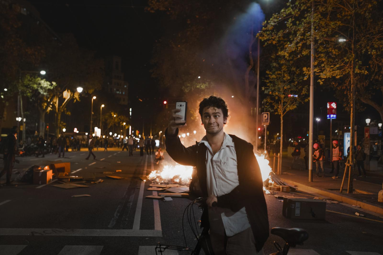 """A young man takes a selfie while the center of Barcelona was tense at various points of Passeig de Gracia, Pau Claris, and Diagonale because of police and protesters' actions to deal with the burning of some containers and the creation of barricades to contain the police advance. The riots in Barcelona have left significant damages to street furniture. Fomento Ministry counted the cost at millions of euros. The images of concentrations have also provoked the teasing of many citizens. Have been criticized for the exhibitionism, on many occasions in a comic tone, for the conditions in which youths are found in the photos on social networks. Especially when students occupied Plaza Universidad with camping tents and the """"spokespersons"""" have posted a video asking families, businesses and individuals to help their 'demonstration' by bringing them solidarity and various products (tents, garbage bags) with the specification: """"cookies and chocolate no, we have enough"""". (October 26,2019. Barcelona, Spain)"""