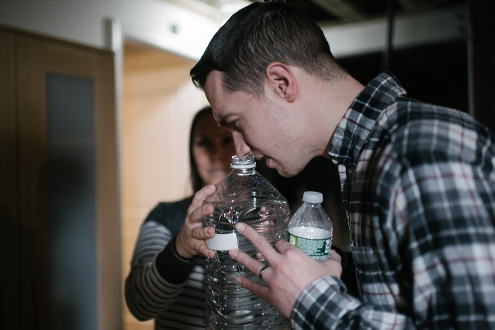 Jon Tarr, 31, smells water that him and his wife, Erica, stored away to get checked at their home in Glen Mills, PA. on Thursday, January 16, 2020. The Tarrs have been dealing with contaminated water since the summer of 2019. They take showers at family and friends� homes and Erica�s brother-in-law brings her water for the water buffalo. Photo by Hannah Yoon