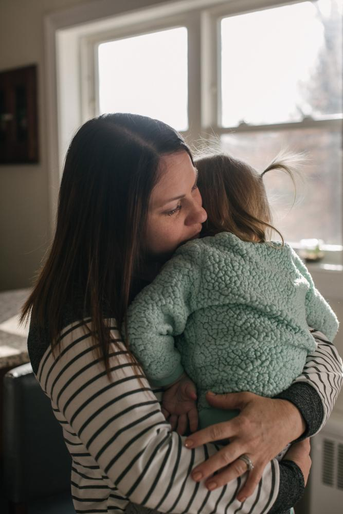 Erica Tarr, 31, left, hugs her daughter, Evie, 2, at their home in Glen Mills, PA. on Thursday, January 16,2020. The Tarr family have been dealing with contaminated water in their home and believe it has to do with the Mariner East Pipeline being built near her house. Photo by Hannah Yoon