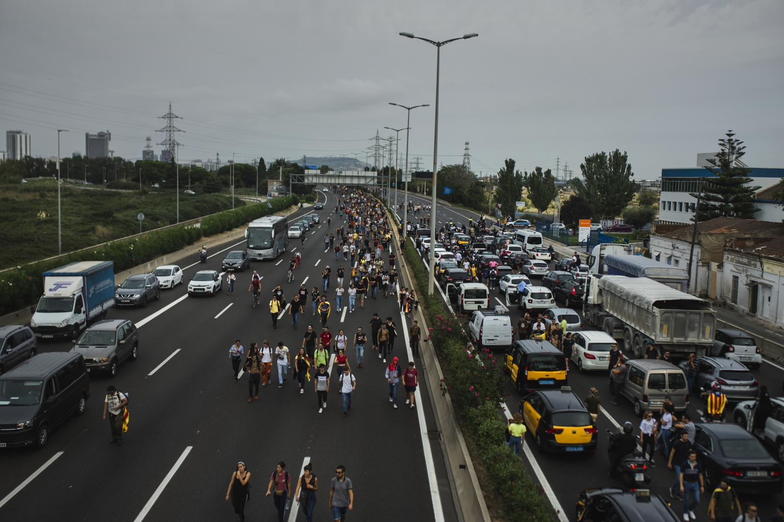 People walking on the highway to head to the airport. (October 14,2019. Barcelona, Spain)