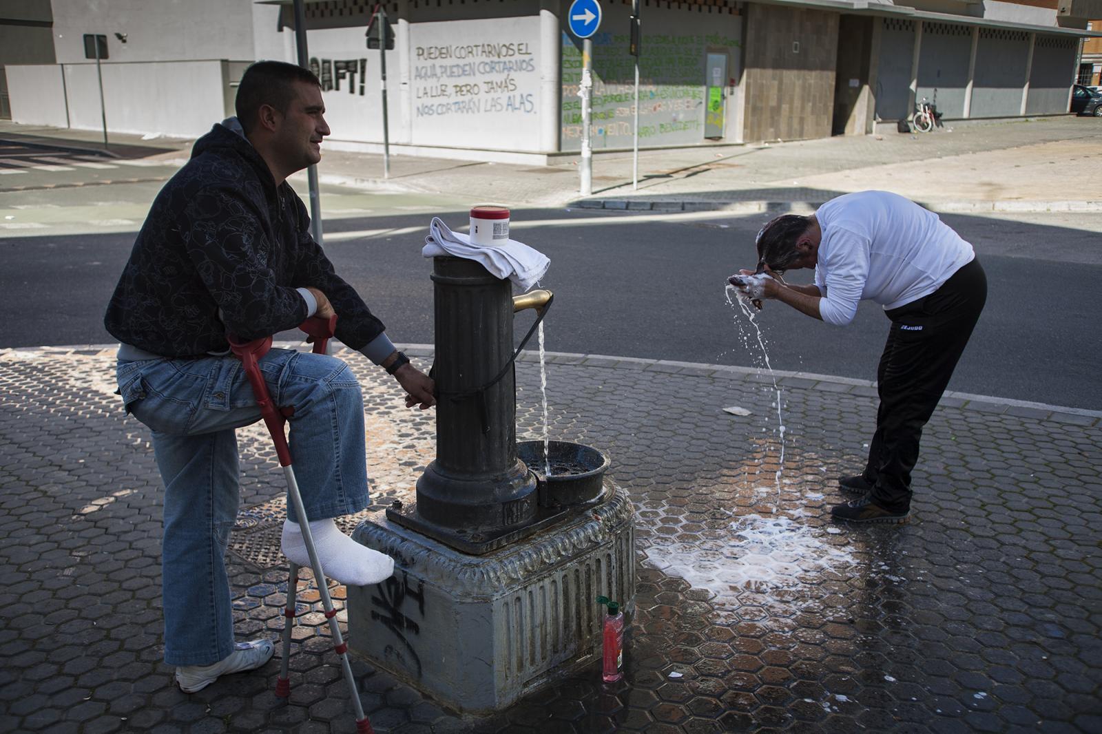 Miguel ayuda a Aguasanta a lavarse el pelo. La falta de agua corriente hace que los vecinos de la corrala utilicen la fuente también como lugar de aseo.