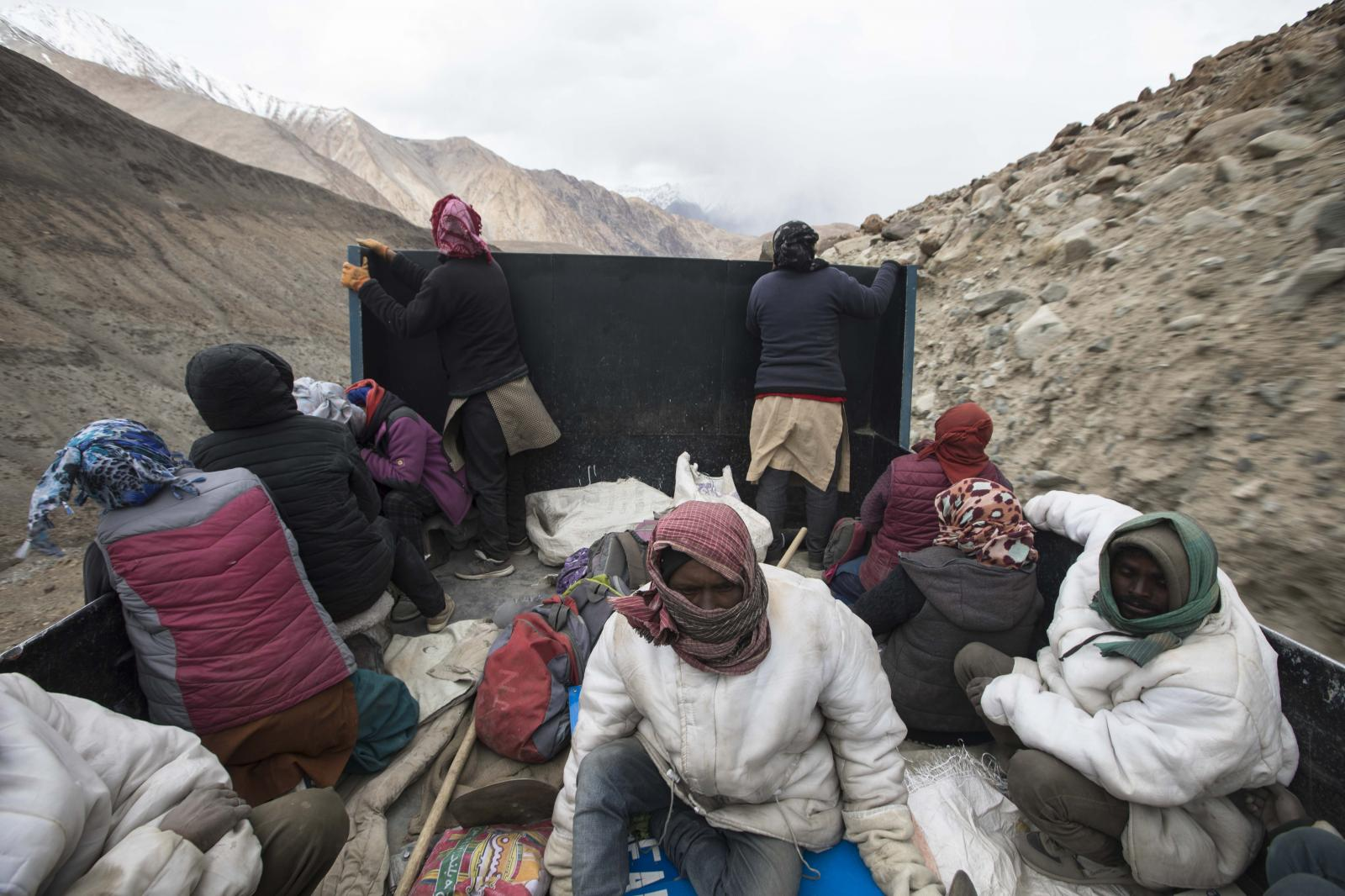 Road maintenance workers from India's low-lying eastern Jharkhand state and local workers from Ladakh ride on the back of a truck at the end of their working day along Pangong Lake road.