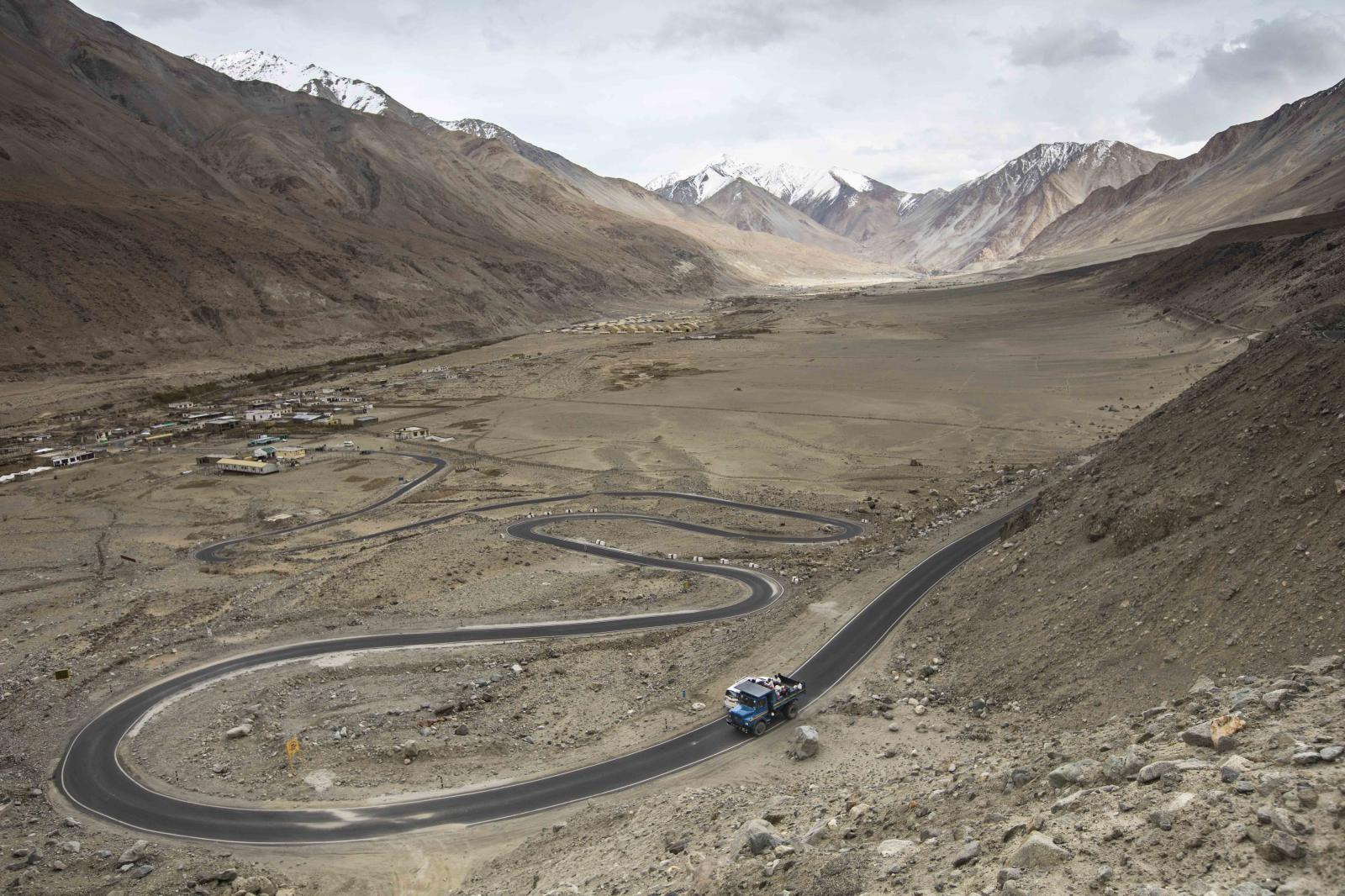 Road maintenance workers from Jharkhand state and local workers from Ladakh ride on the back of a truck at the end of their working day along Pangong Lake road in northern India's Ladakh region.