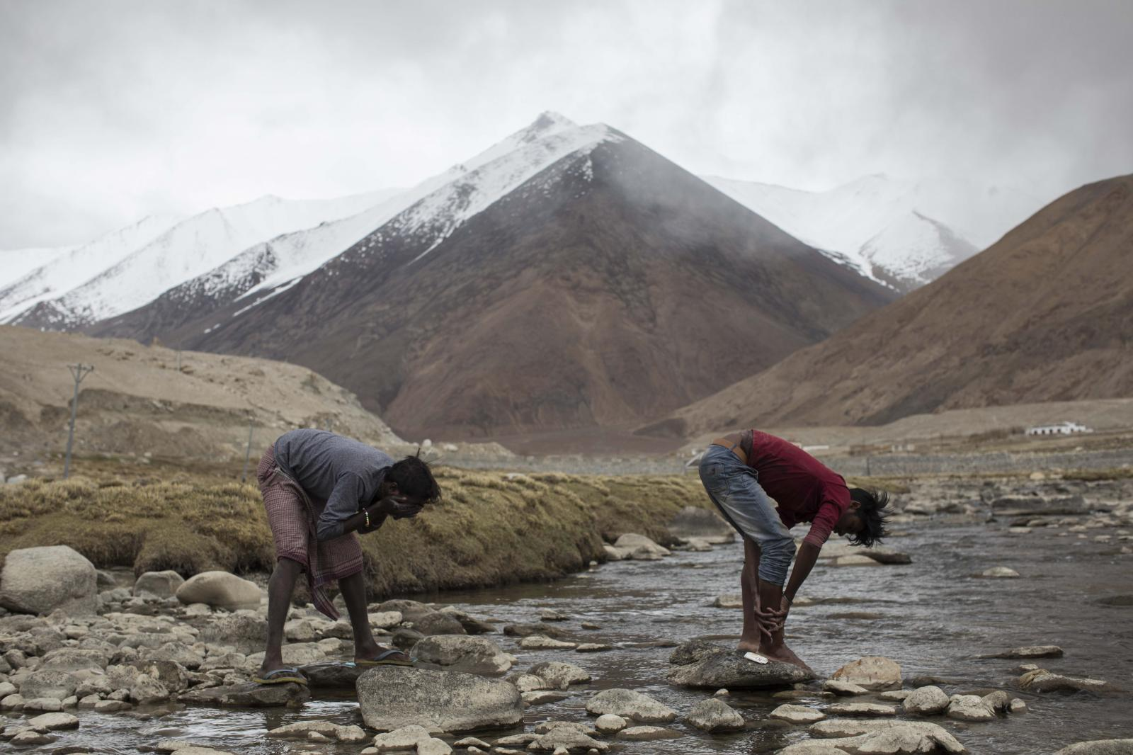 Raju Dheri (R), 19, and Surinder Tudu, 22, road maintenance workers from Jharkhand state, wash in a river next to their campsite after a day's work near Tangtse village in northern India's Ladakh region.
