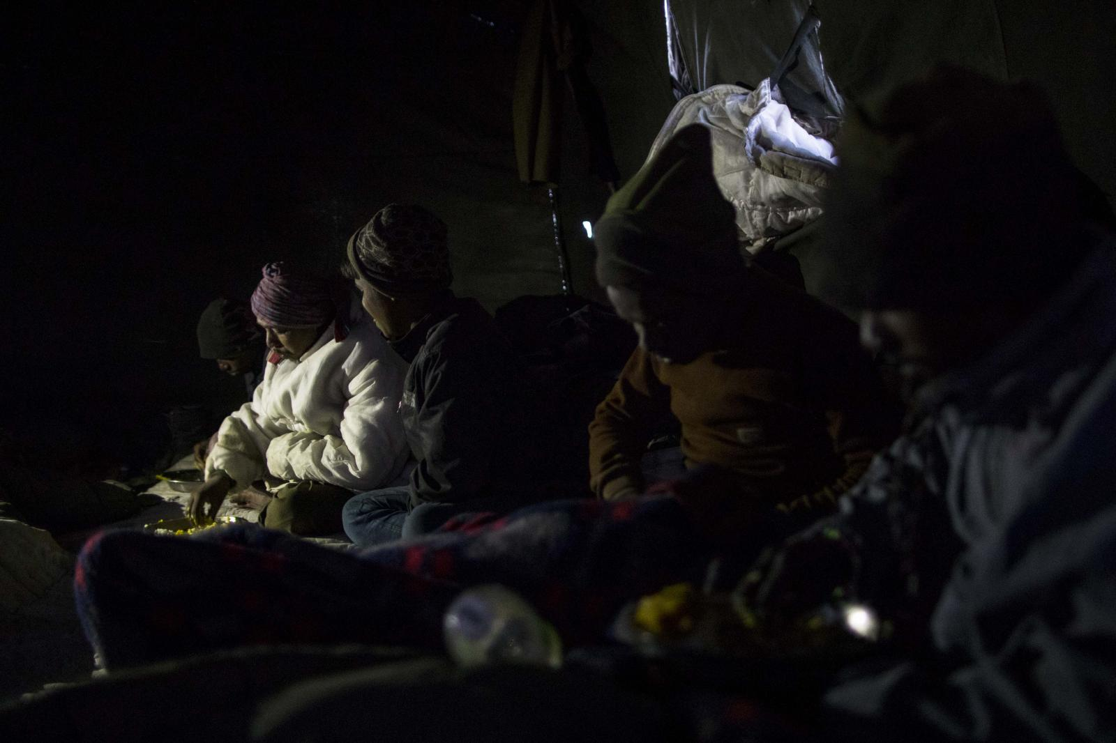 Road maintenance workers from India's low-lying eastern Jharkhand state eat dinner inside their tent at their campsite near Tangtse village in northern India's Ladakh region.