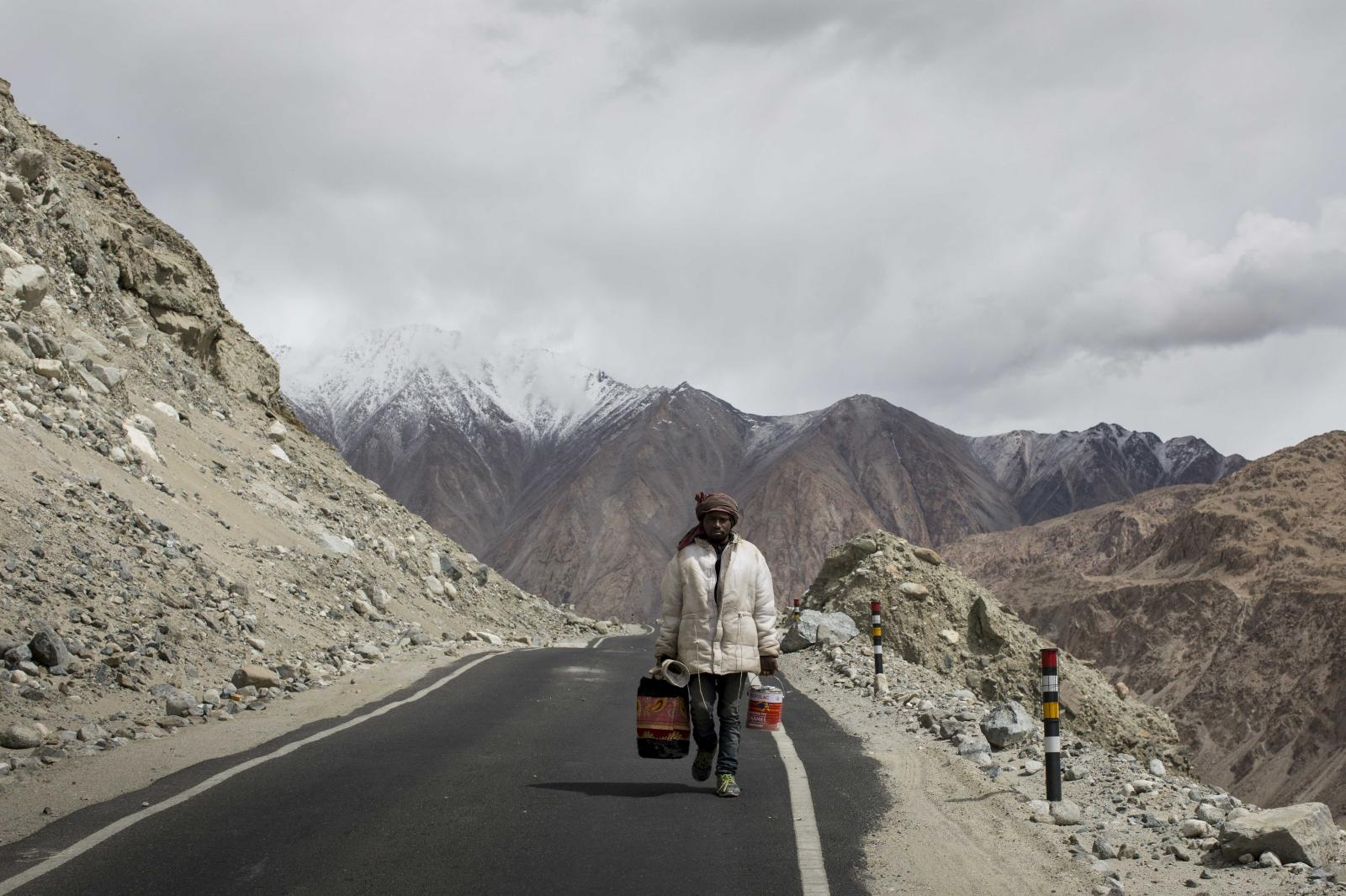 A road maintenance worker from India's low-lying eastern Jharkhand state, carries buckets of paint to restore road markers along Pangong Lake road near the Chang La pass in northern India's Ladakh region.
