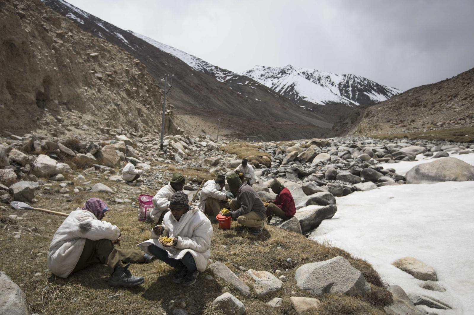 Road maintenance workers from India's low-lying eastern Jharkhand state eat lunch while labouring along Pangong Lake road near the Chang La pass in northern India's Ladakh region.