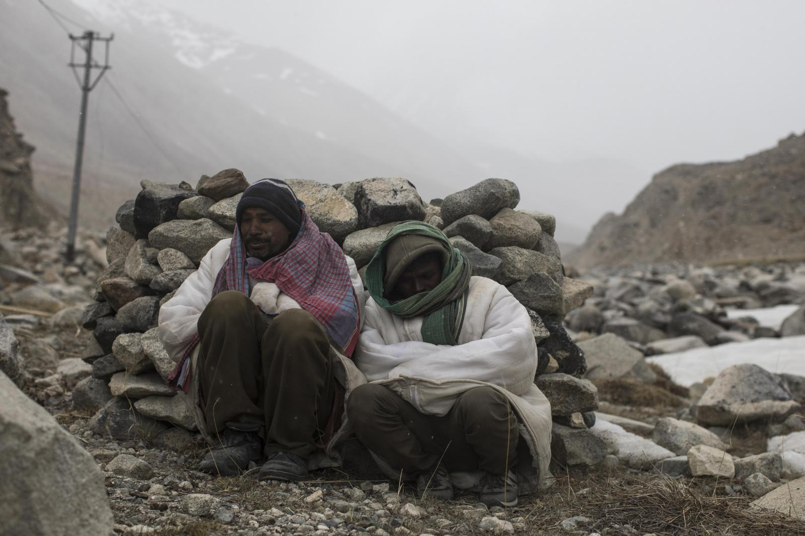 Raj Shekhar (L), 33, and Tej Narayan, 30, road maintenance workers from Jharkhand state, take shelter behind rocks during inclement weather along Pangong Lake road near the Chang La pass in northern India's Ladakh region.