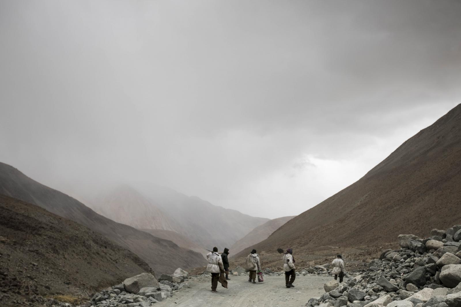 Road maintenance workers from Jharkhand state head back to their campsite following a day's work along Pangong Lake road near the Chang La pass in northern India's Ladakh region.