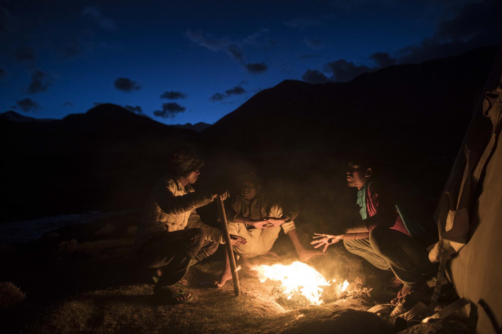 (L-R) Chota Montu, 25, Raj Kumar, 19, and Raju Dheri, 19, road maintenance workers Jharkhand state, warm up around a bonfire at their campsite near Tangtse village in northern India's Ladakh region.