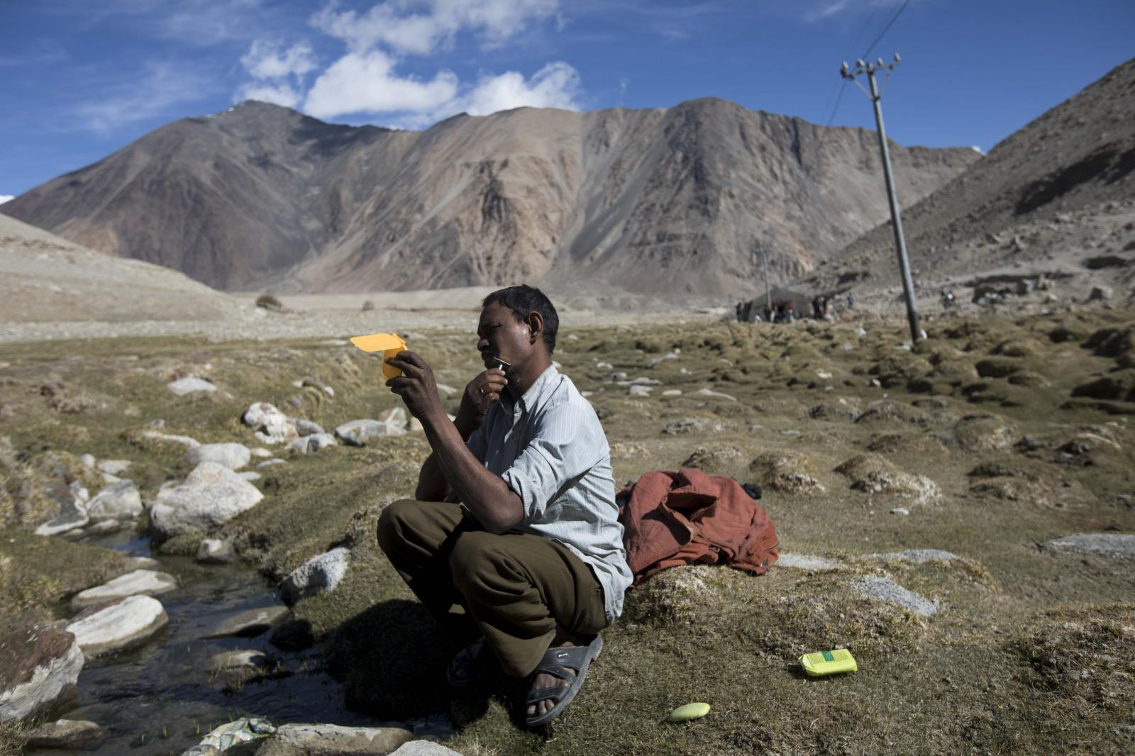 Raj Shekhar, 33, a road maintenance worker from India's low-lying eastern Jharkhand state, shaves on his day off at his campsite near Tangtse village in northern India's Ladakh region.