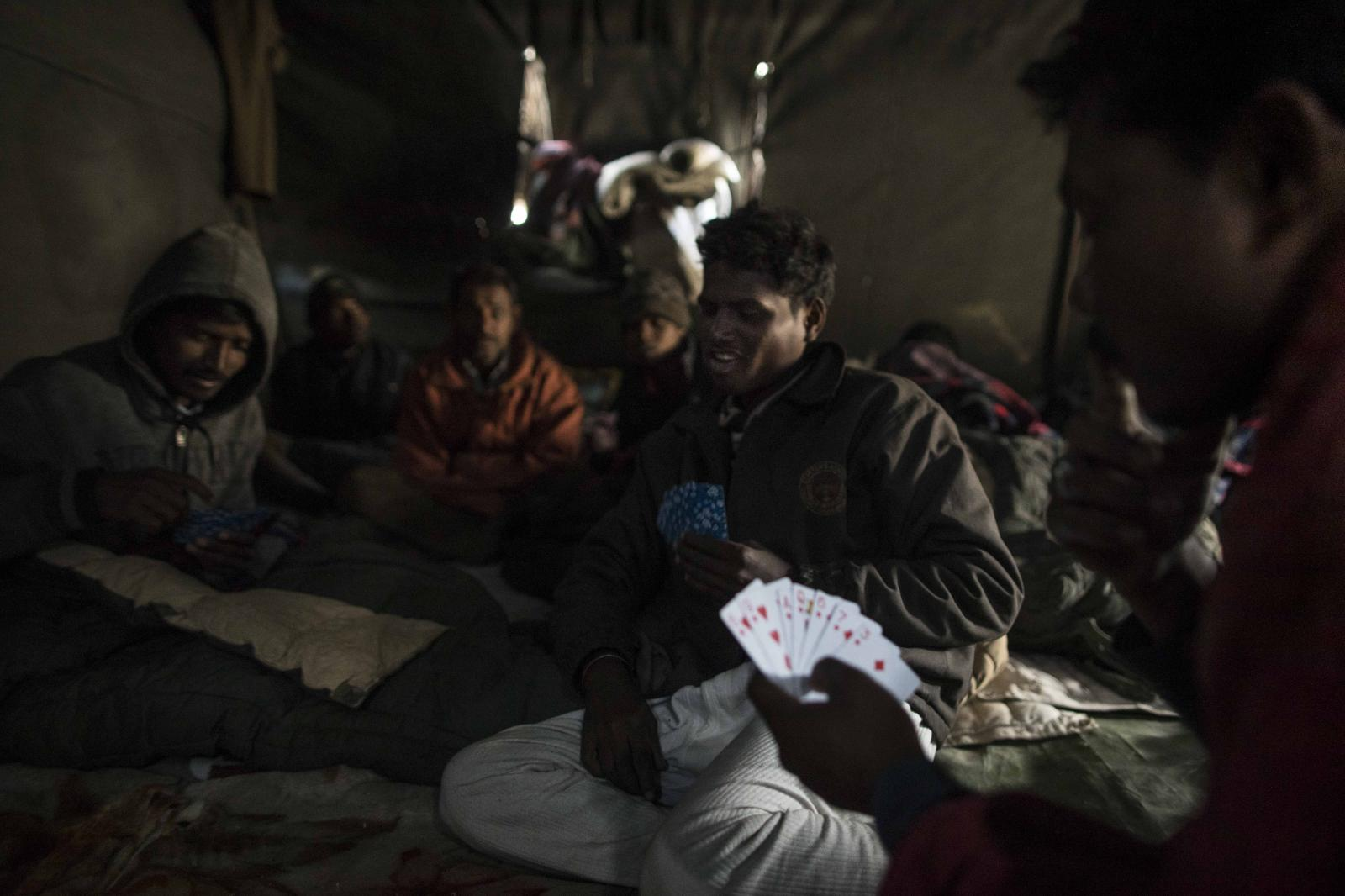 Road maintenance workers from India's low-lying eastern Jharkhand state play cards inside their tent following a day's work at their campsite near Tangtse village in northern India's Ladakh region.