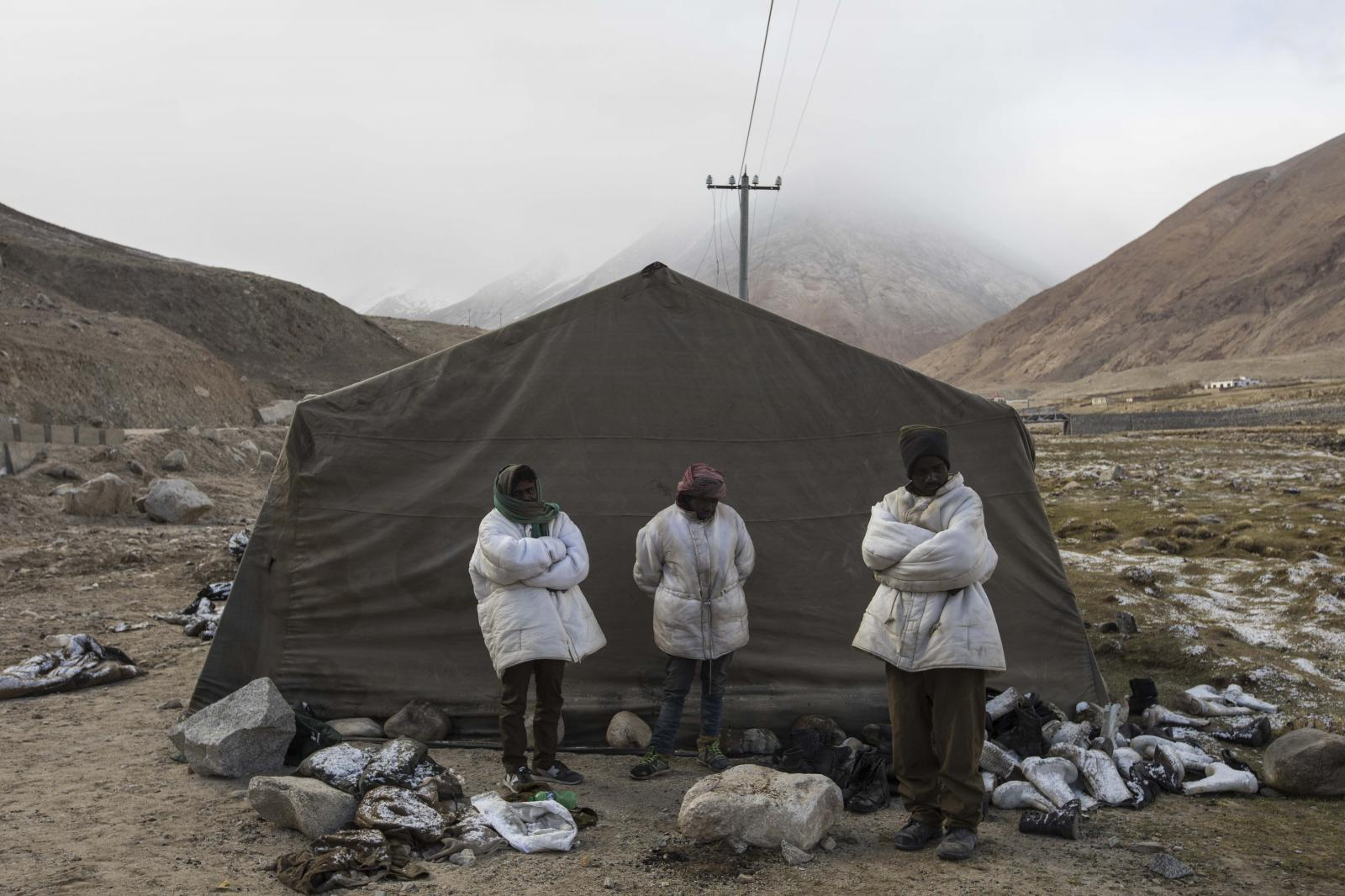 (L-R) Tej Narayan, 30, Rajesh Manji, 28, and Sunil Tutu, 33, road maintenance workers from Jharkhand state, wait for transportation to their work site near Tangtse village in northern India's Ladakh region.