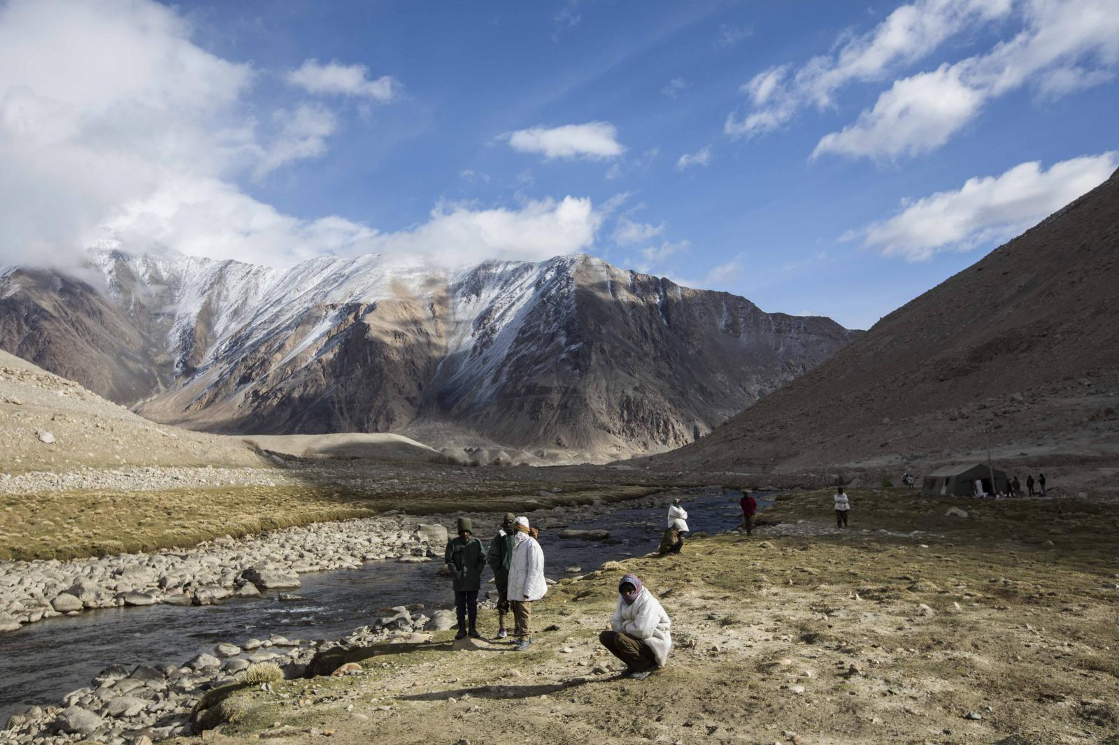 Road maintenance workers from Jharkhand state warm up with the first rays of the sun, as they wait for a ride to their worksite at their camping grounds near Tangtse village in northern India's Ladakh region.