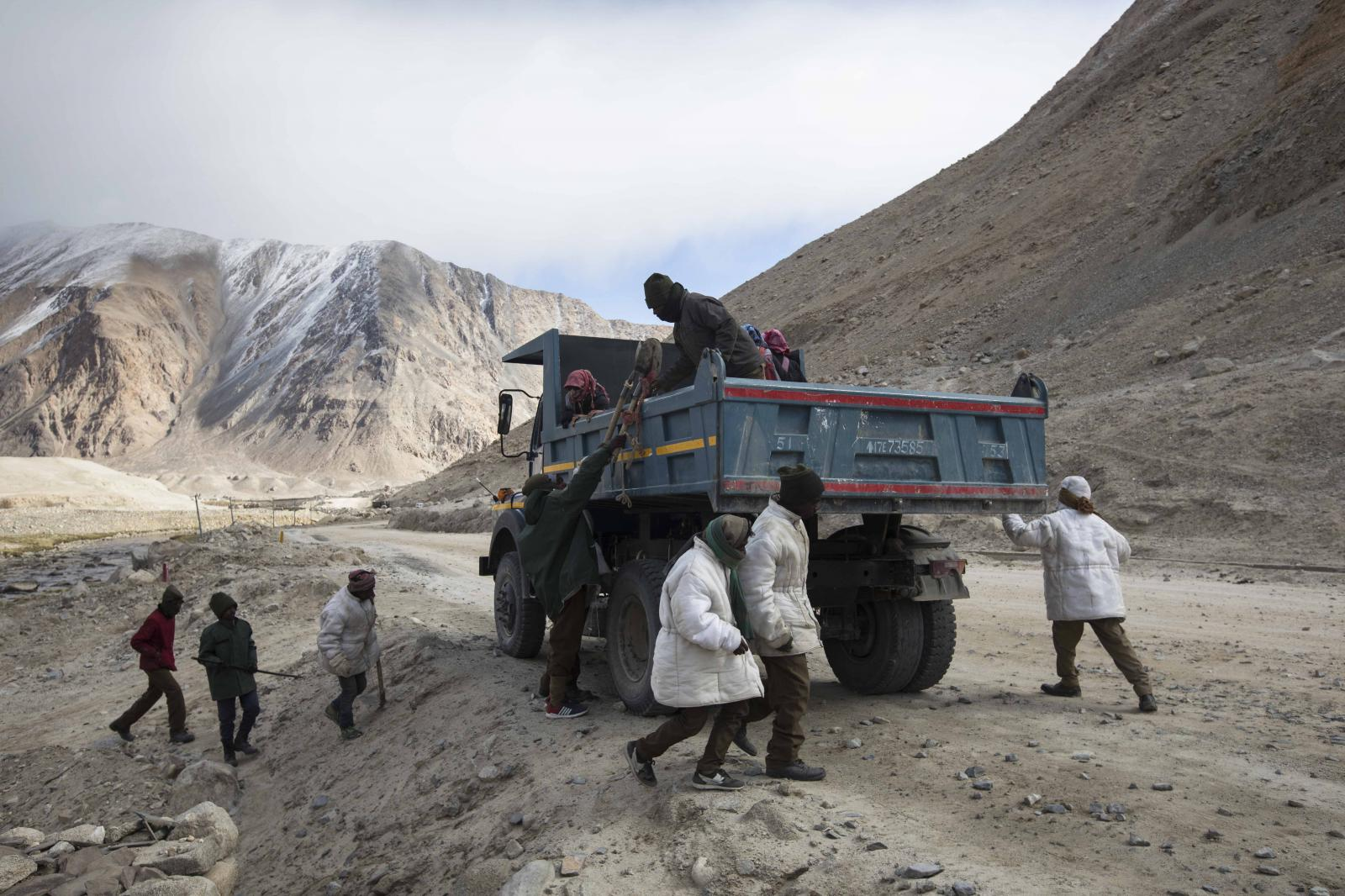 Road maintenance workers from Jharkhand jump at the buck of a truck collecting them in the morning from their campsite near Tangtse village be in northern India's Ladakh region.