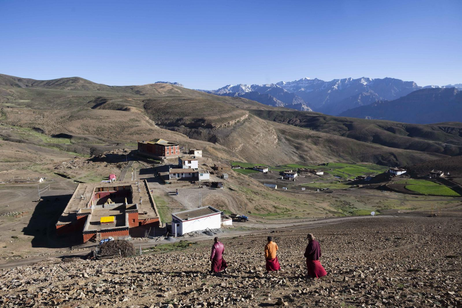 Buddhist monks walk down from a hill overlooking Tnagyud Gompa monastery in Komik village, in Spiti Valley of the Indian northern state of Himachal Pradesh.