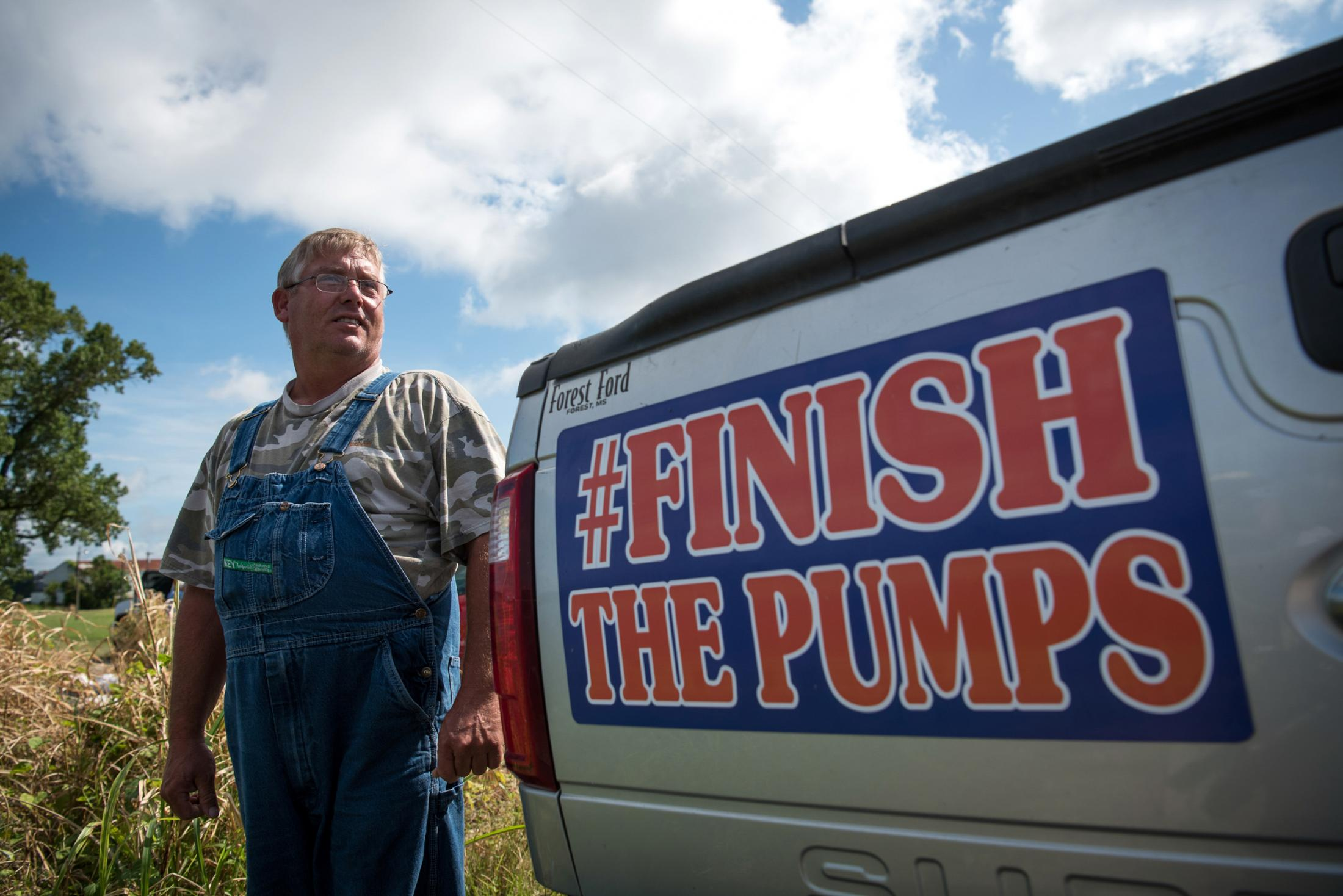 "Rodney Porter poses for a portrait neaxt to his pickup truck in Valley Park, Mississippi on July 20, 2019. Many residents have decorated their vehicles with the ""Finish The Pumps"" hashtag to spread flood awareness."