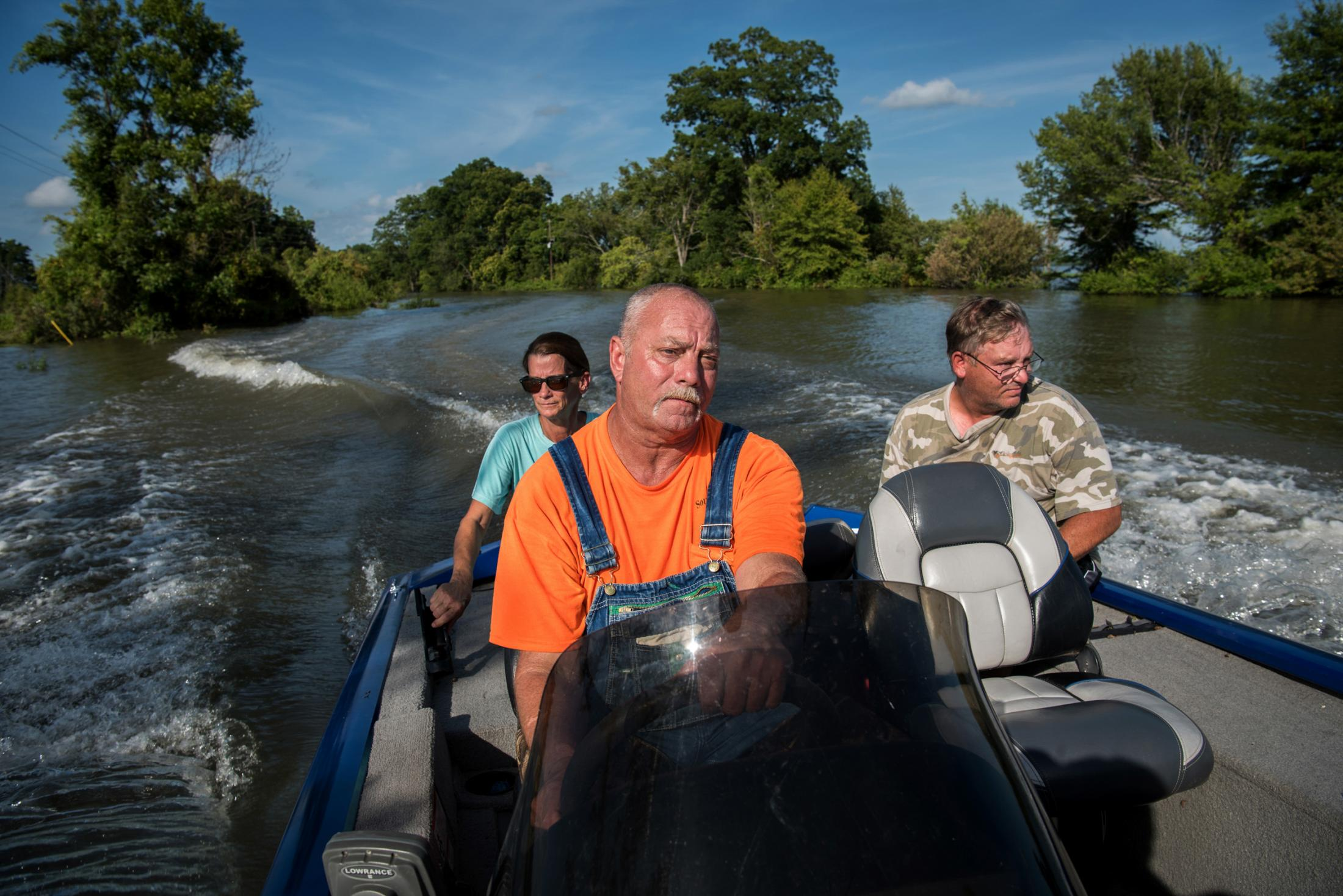 "Carmen Hancock (left to right), James Hancock and Rodney Porter boat down a flooded road near their homes in Valley Park, Mississippi on July 16, 2019. They've spent the past five months helping their elderly neighbors survive in their homes surrounded by floodwater. ""We're living by the good Lord to do what's right,"" said James. ""There's a number of older people living in this neighborhood, and It's just the right thing to do. When the going gets tough, the tough gets going. That's what I live by. You do what has to be done."" Photo by Rory Doyle for the Guardian."