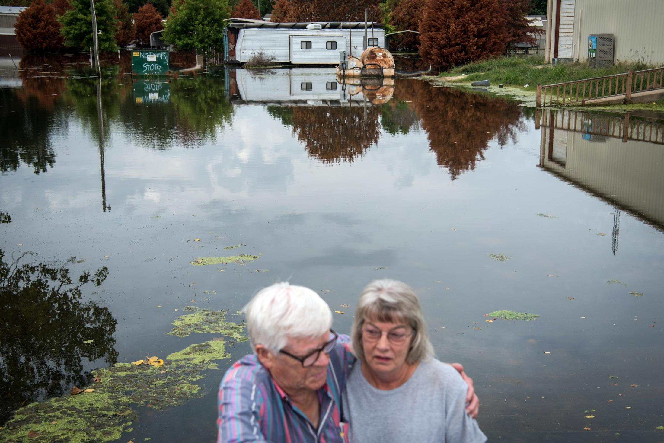 Don Johnson, left, hugs his daughter, Beverly Cooper, near floodwater at Eagle Lake in Warren County, Mississippi on July 21, 2019. Cooper is temporarily living in a camper as a result of the flood. Photo by Rory Doyle for The Guardian.