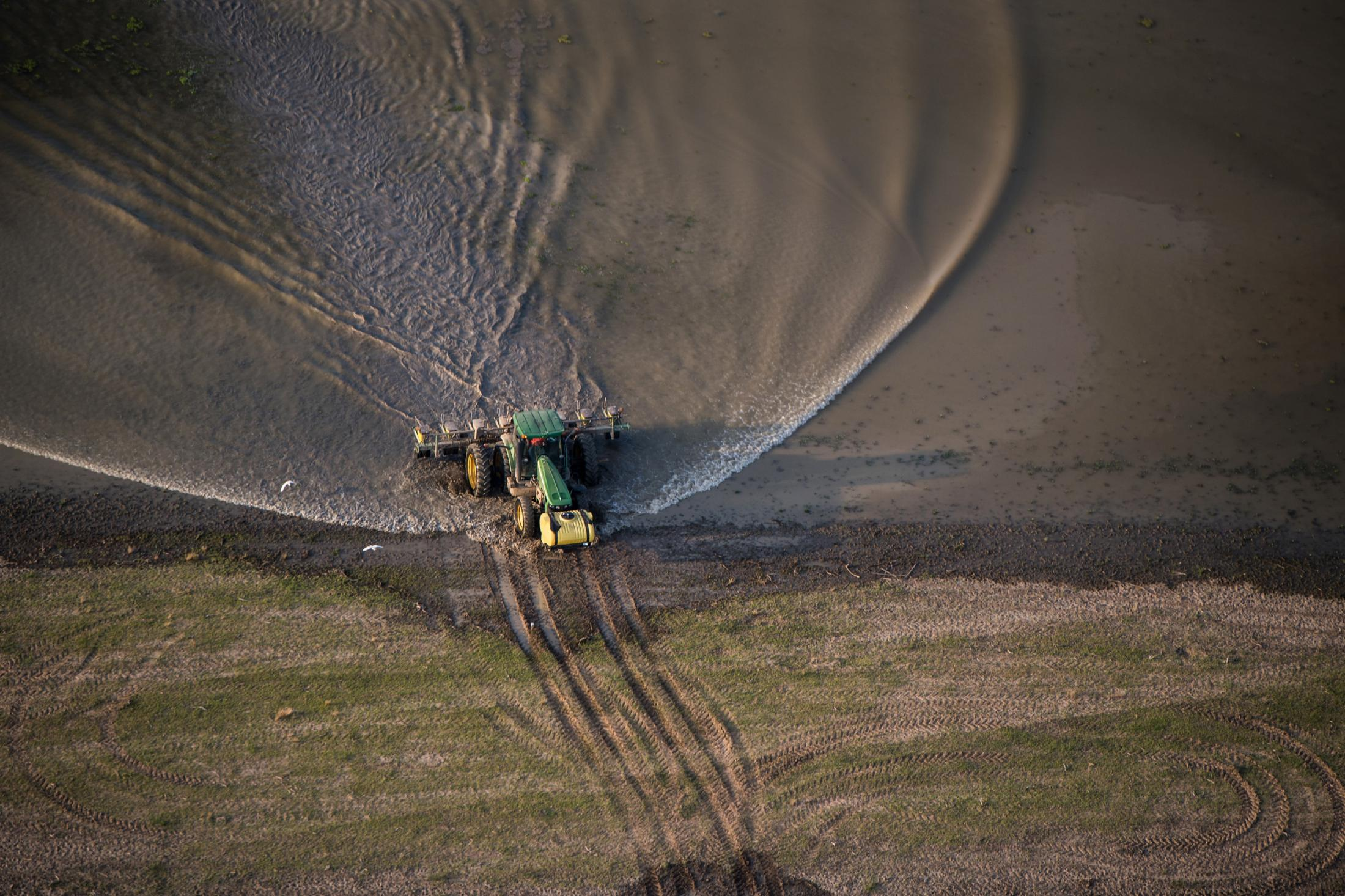 A farmer exists floodwater and navigates the little dry land remaining on his property in the lower Mississippi Delta June 14, 2019.