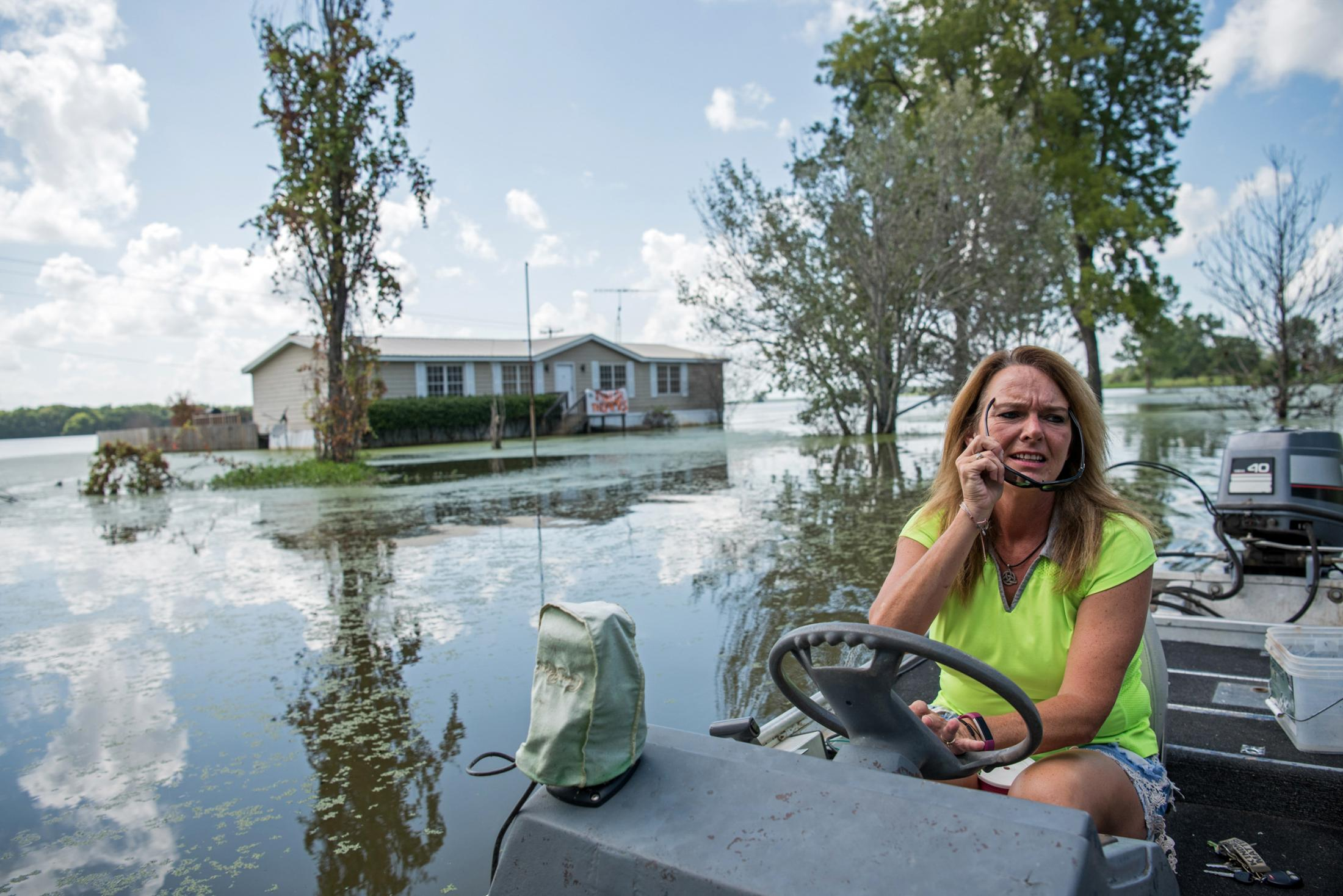 "Stormy Deere boats outside her home in Warren County, Mississippi on July 16, 2019. Deere's home was built high enough that it didn't succumb to the floodwater, but she did have to boat in and out of her property beginning in March. ""The isolation is tough,"" said Deere. ""It's such a pain having to boat where I use to drive. The emotional effect is awful. You think you'll see the light of day when the water drops a little, and then it pops right back up again. It's really hard. This isn't fair — just because we have a lower population, and we have a lower income per household, we still matter. We should be treated equally."" Photo by Rory Doyle for The Guardian."