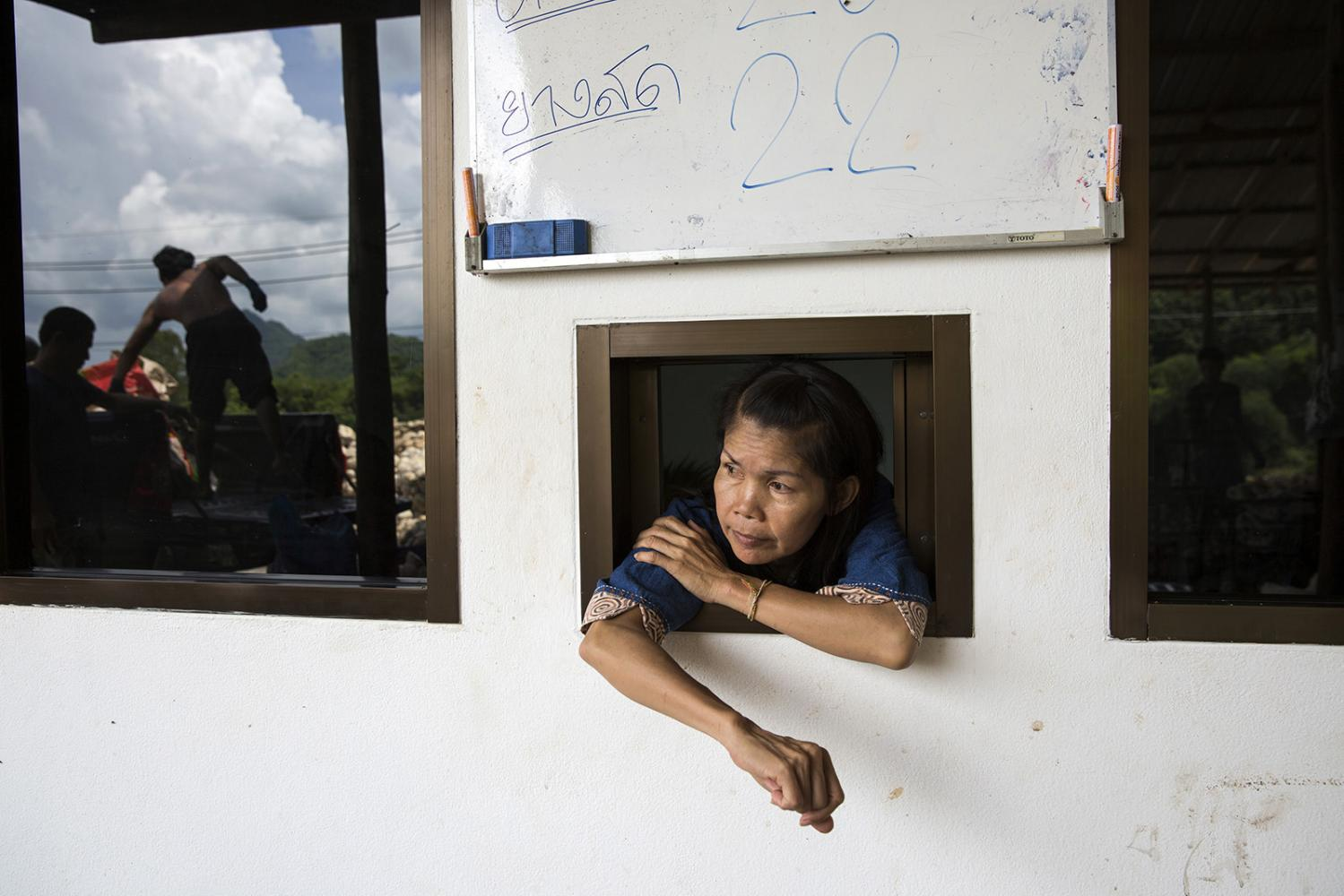 Pornthip Hongchai, a core-member of Khon Rak Ban Kerd, watches workers unload rubber at her families small rubber processing plant. A continued struggle takes a huge economic tole on families who find it difficult to balance their normal life with protest activities.