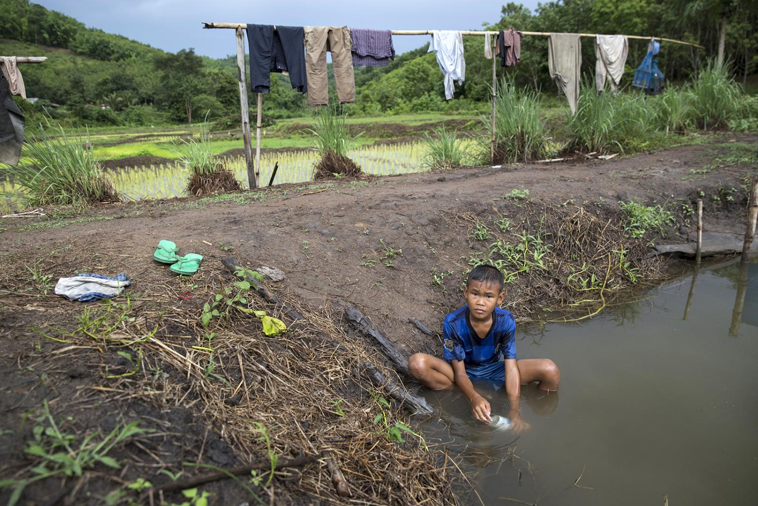 A boy plays in a small pond a few miles outside the community. In areas close to the mine parents have stopped their children playing in the ponds and rivers for fear of them becoming sick.