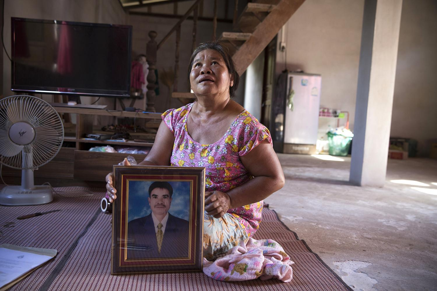 A lady living in Na Nong Bong village shows a portrait of her husband who recently passed away prematurely. Results from a blood test taken by the local health authorities showed that the concentration of arsenic in his blood was above normal.
