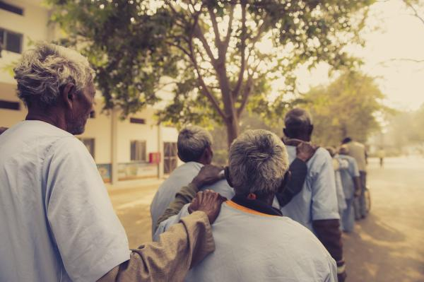Men hold shoulders for guidance as they walk towards the operating theatre in Chitrakoot, India.