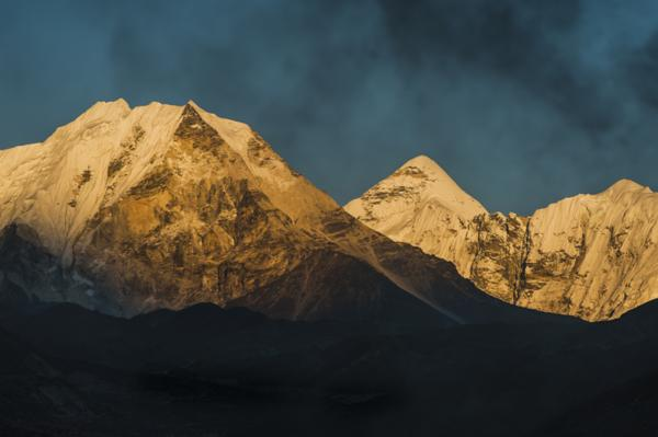 Smoke from a village home passes over the mountains in Dingboche Nepal.