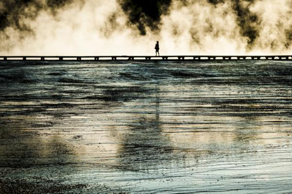A women walks on a plank overlooking a geyser in Yellowstone National Park, California.