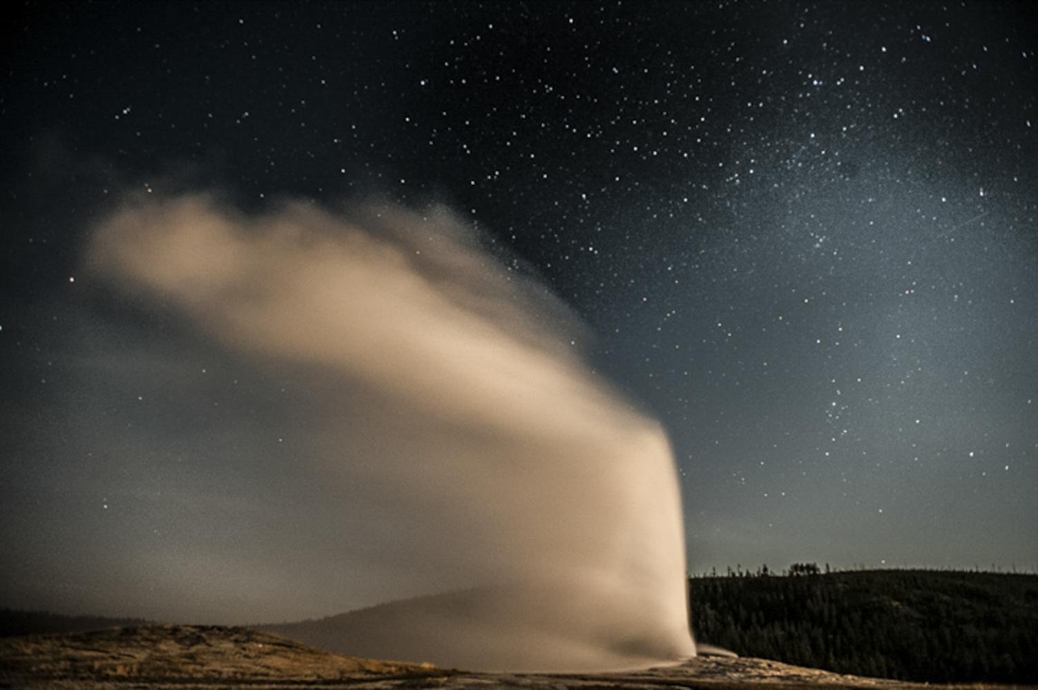 Old Faithful Geyser after dark in Yellowstone National Park.